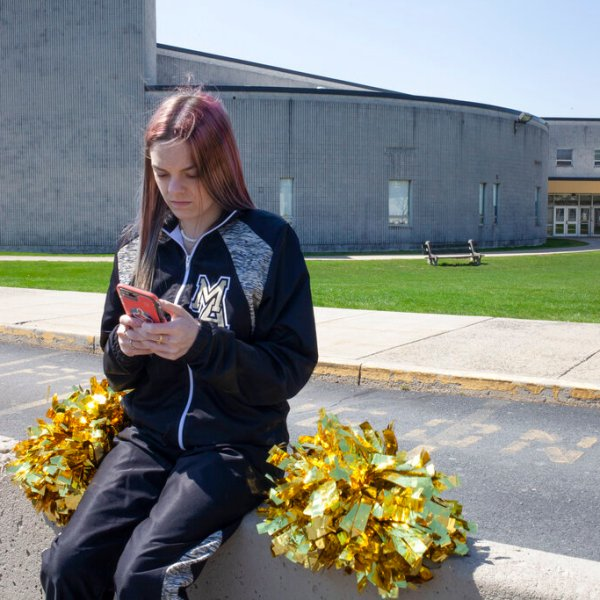 In this April 4, 2021, file photo provided by the American Civil Liberties Union, Brandi Levy wears her cheerleading outfit as she looks at her mobile phone outside Mahanoy Area High School in Mahanoy City, Pa. The Supreme Court ruled Wednesday, June 23, 2021, that the public school wrongly suspended Levy from cheerleading over a vulgar social media post she made after she didn't qualify for the varsity team. (Danna Singer/ACLU via AP, File)