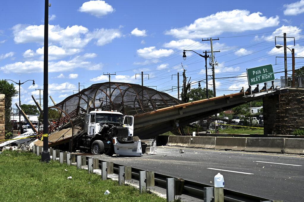 A truck sits under a collapsed pedestrian bridge along Kenilworth Avenue & Polk Street Northeast in Washington, Wednesday, June 23, 2021. (Marvin Joseph/The Washington Post via AP)