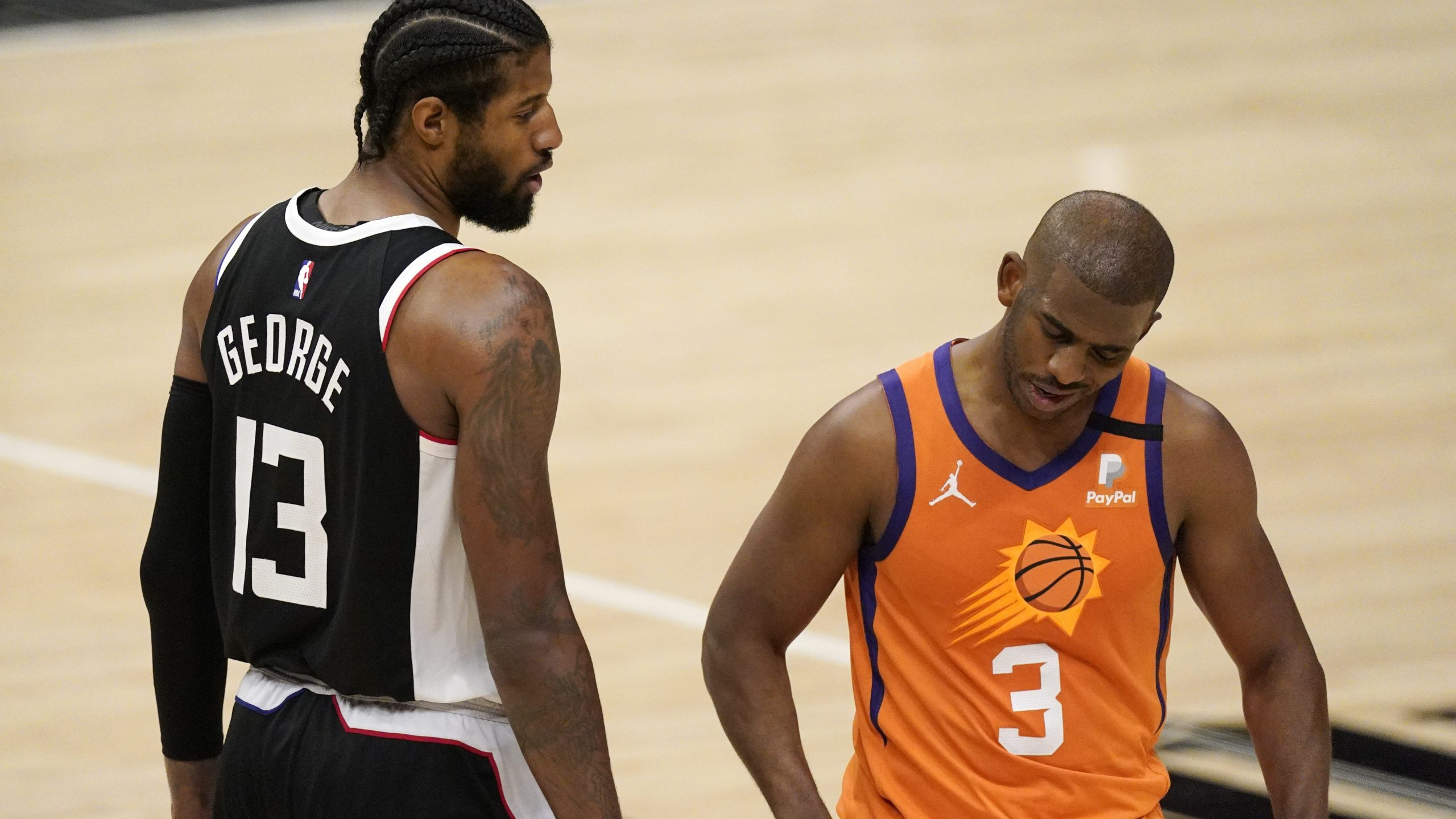 Los Angeles Clippers guard Paul George, left, tries to talk to Phoenix Suns guard Chris Paul during the second half in Game 3 of the NBA basketball Western Conference Finals in Los Angeles on June 24, 2021. (Mark J. Terrill / Associated Press)