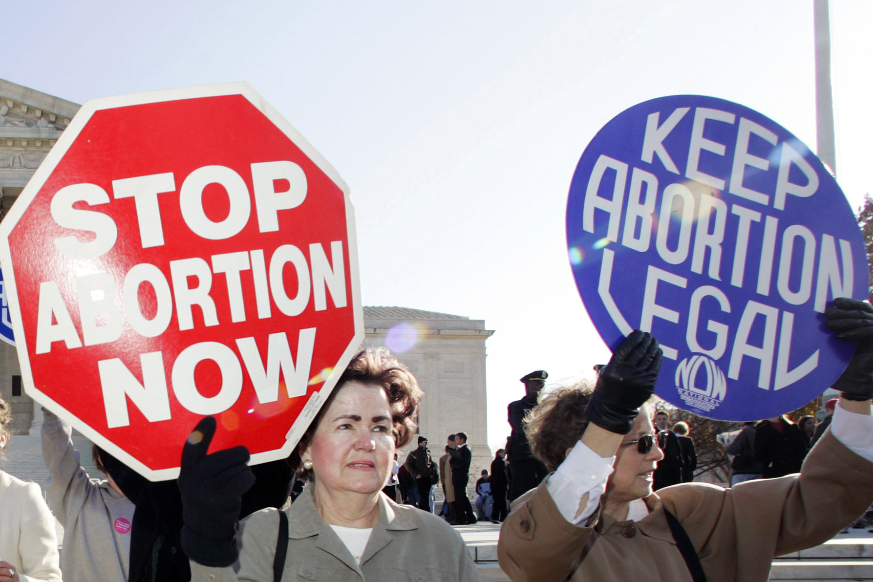 In this Nov. 30, 2005 file photo, an anti-abortion supporter stands next to a pro-choice demonstrator outside the U.S. Supreme Court in Washington. The new poll from The Associated Press-NORC Center for Public Affairs Research finds 61% of Americans say abortion should be legal in most or all circumstances in the first trimester of a pregnancy. However, 65% said abortion should usually be illegal in the second trimester, and 80% said that about the third trimester. (AP Photo/Manuel Balce Ceneta)
