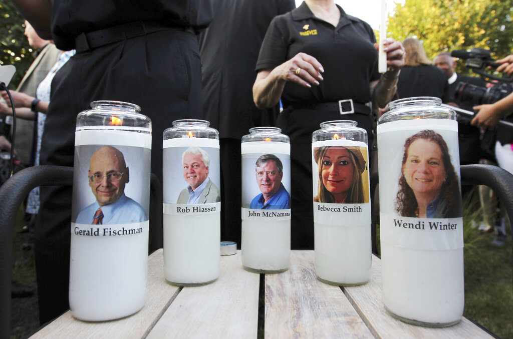 In this June 29, 2018, file photo, pictures of five employees of the Capital Gazette newspaper adorn candles during a vigil across the street from where they were slain in the newsroom in Annapolis, Md. (AP Photo/Jose Luis Magana, File)