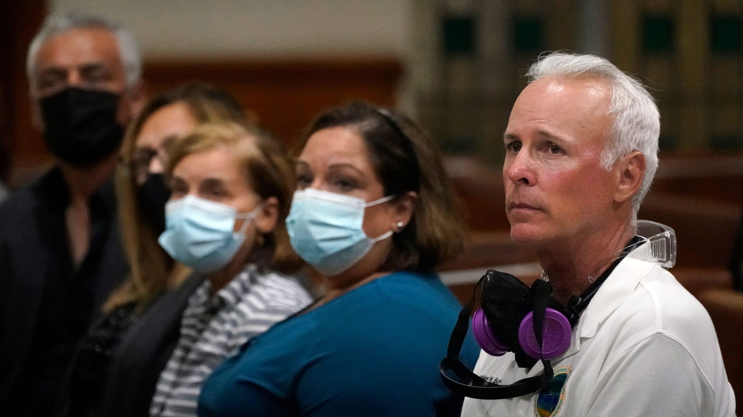 Surfside, Fla., Mayor Charles Burkett, right, joins worshipers, late Saturday, June 26, 2021, during a prayer vigil for the victims and families of the Champlain Towers collapsed building in Surfside, at the nearby St. Joseph Catholic Church in Miami Beach, Fla. Many people were still unaccounted for two days after Thursday's fatal collapse. (AP Photo/Wilfredo Lee)