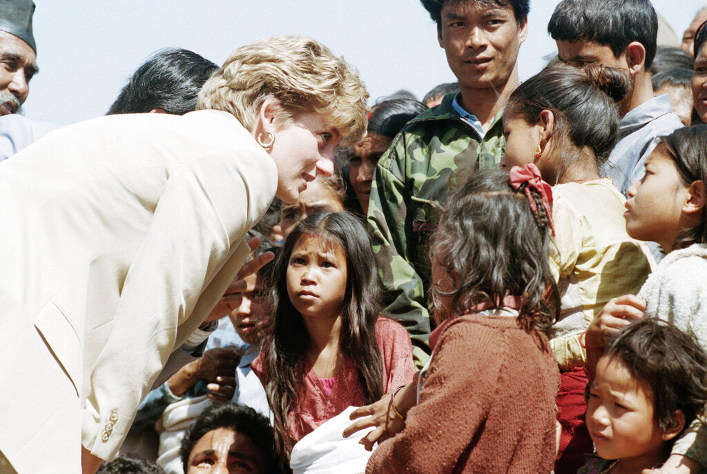 In this file photo dated Friday, March 5, 1993, Britain's Diana talks with Nepalese children in the village of Panauti, in the foothills of the Himalayas, as some thousands of villagers, mostly children, turned out to greet her. (AP Photo/Barbara Walton, File)