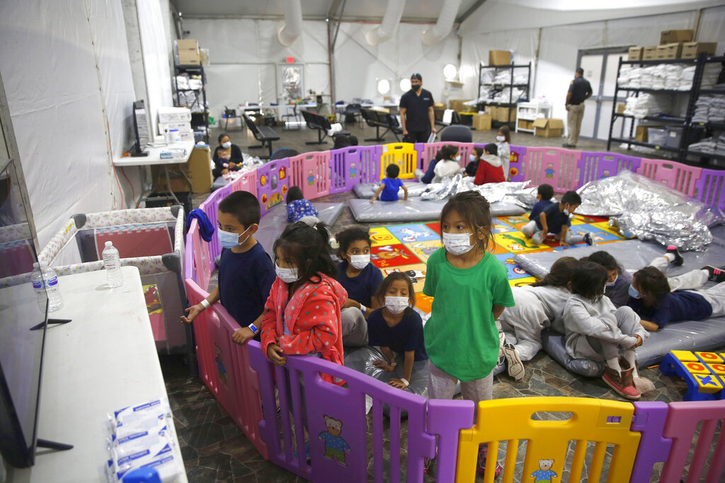 In this March 30, 2021 file photo Young unaccompanied migrants, from ages 3 to 9, watch television inside a playpen at the U.S. Customs and Border Protection facility, the main detention center for unaccompanied children in the Rio Grande Valley, in Donna, Texas. (AP Photo/Dario Lopez-Mills, Pool, File)