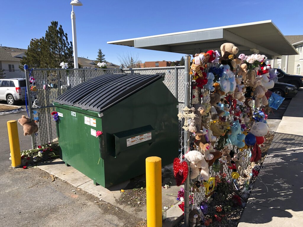 In this Feb. 22, 2021, file photo, stuffed animals and notes of condolences are seen attached to a fence around a dumpster at a Cheyenne, Wyo., apartment complex where a 2-year-old boy was found dead. (AP Photo/Mead Gruver,File)
