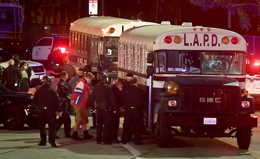 Protesters board a Los Angeles Police Department bus after being arrested in Echo Park in March 2021. (Wally Skalij / Los Angeles Times)