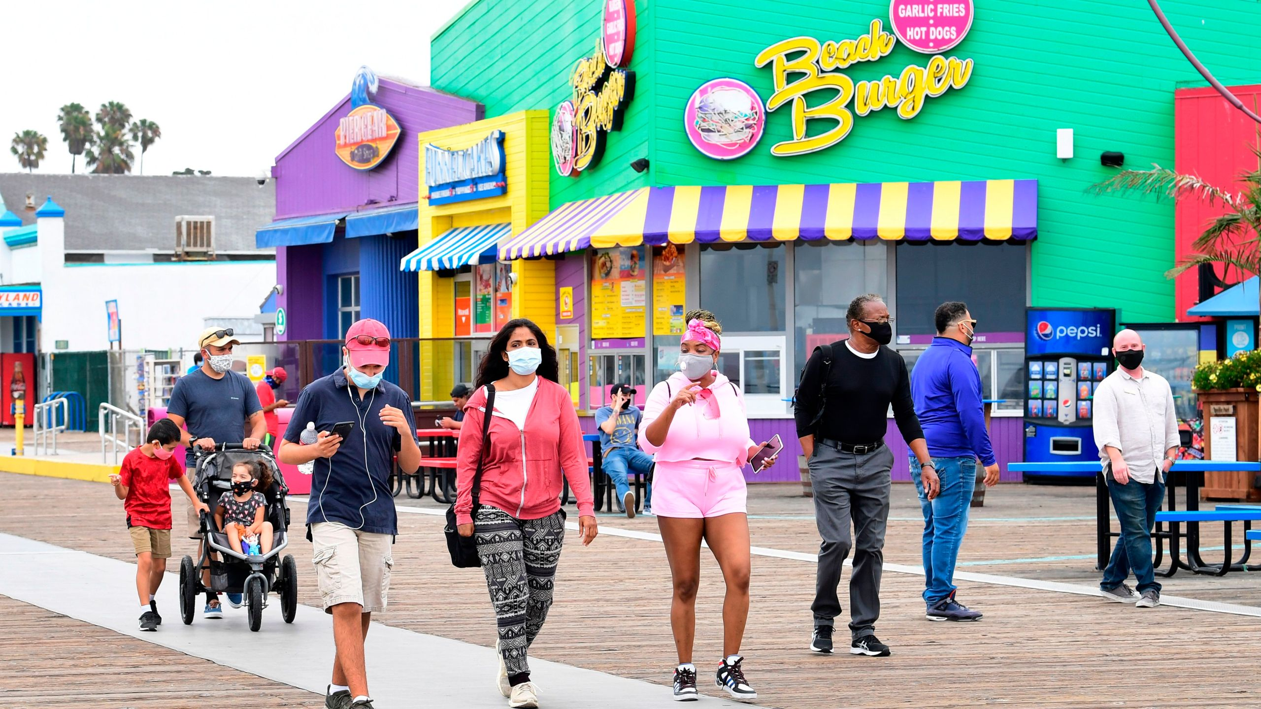 People wearing face masks at Santa Monica Pier on June 26, 2020 in Santa Monica. ( FREDERIC J. BROWN/AFP via Getty Images)