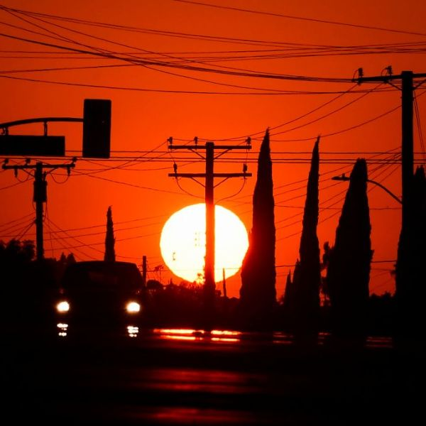 The sun sets behind power lines in Los Angeles on Sept. 3, 2020, ahead of a heat wave prompting a statewide flex alert. (Frederic J. Brown / AFP / Getty Images)
