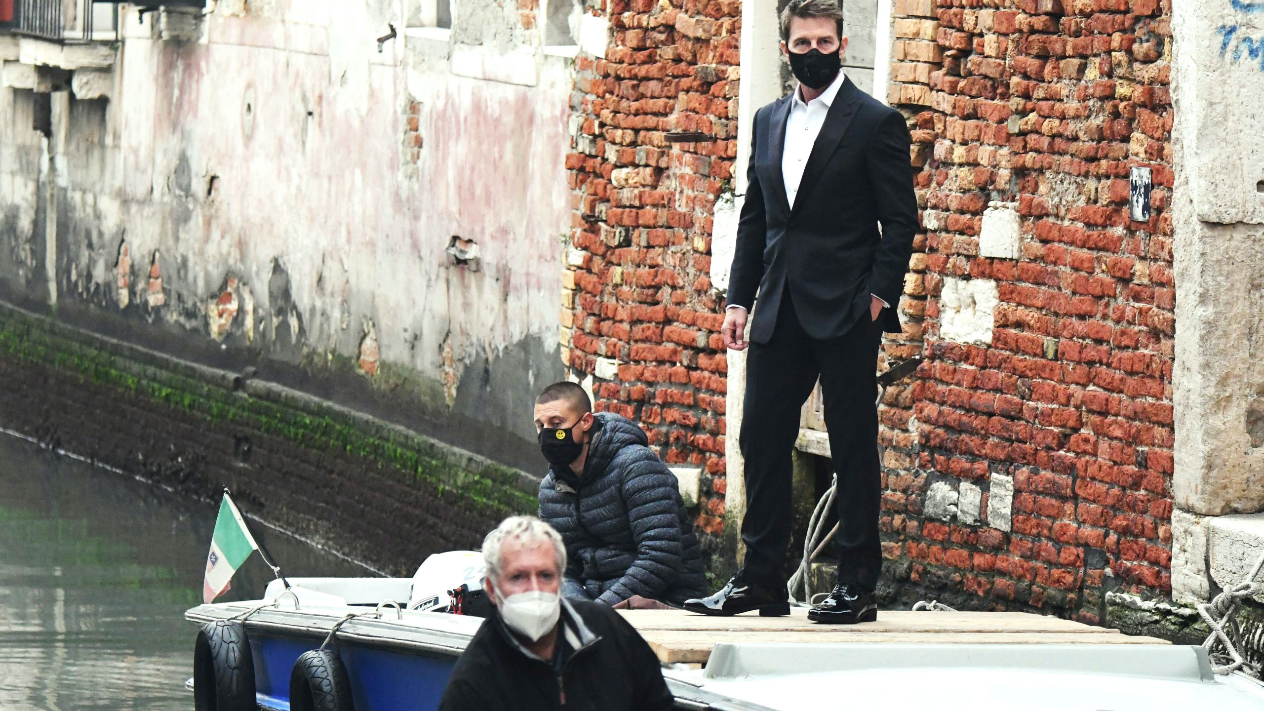"""U.S. actor Tom Cruise stands on a boat during the shooting of the movie """"Mission Impossible: Lybra"""" in Venice on Oct. 20, 2020. (ANDREA PATTARO / AFP via Getty Images)"""