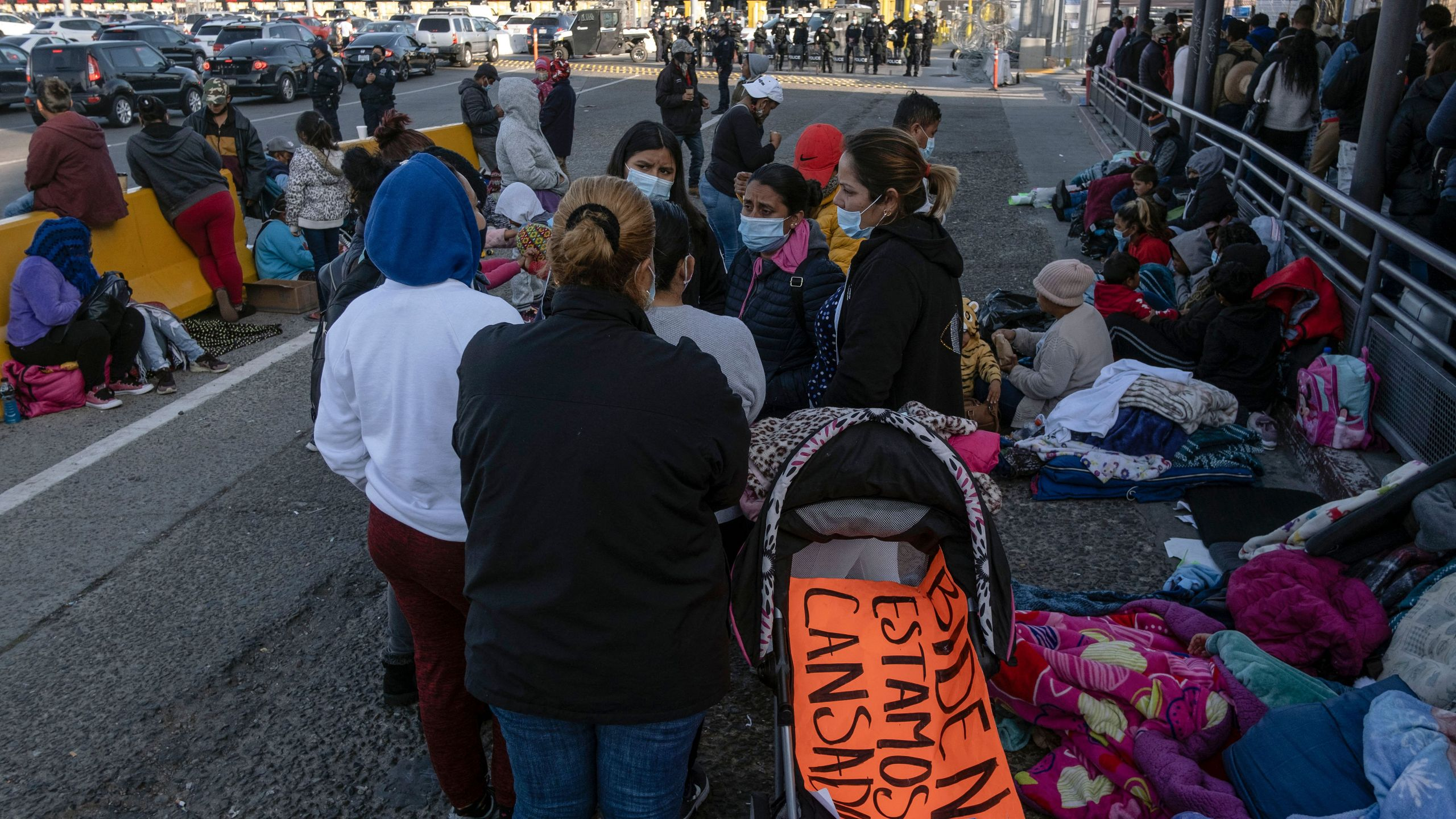 Migrants and asylum seekers are seen after spending the night in one of the car lanes off the San Ysidro Crossing Port on the Mexican side of the US_Mexico border in Tijuana, Baja California state, Mexico on April 24, 2021. (Guillermo Arias / AFP via Getty Images)
