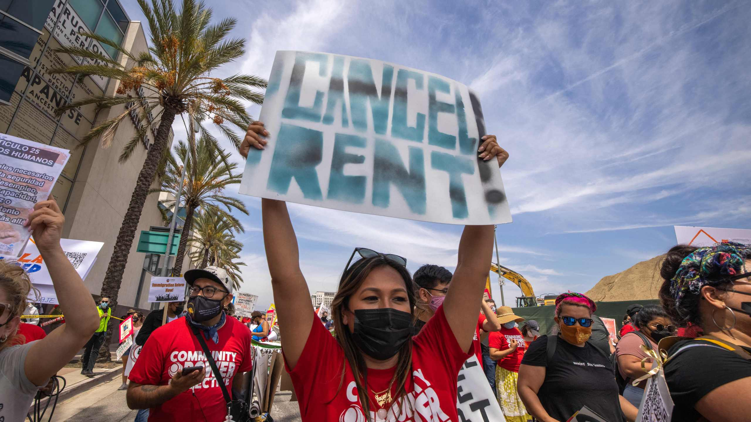 A woman calls for rent relief as a coalition of activist groups and labor unions participate in a May Day march for workers' and human rights in Los Angeles on May 1, 2021. (David McNew / AFP / Getty Images)
