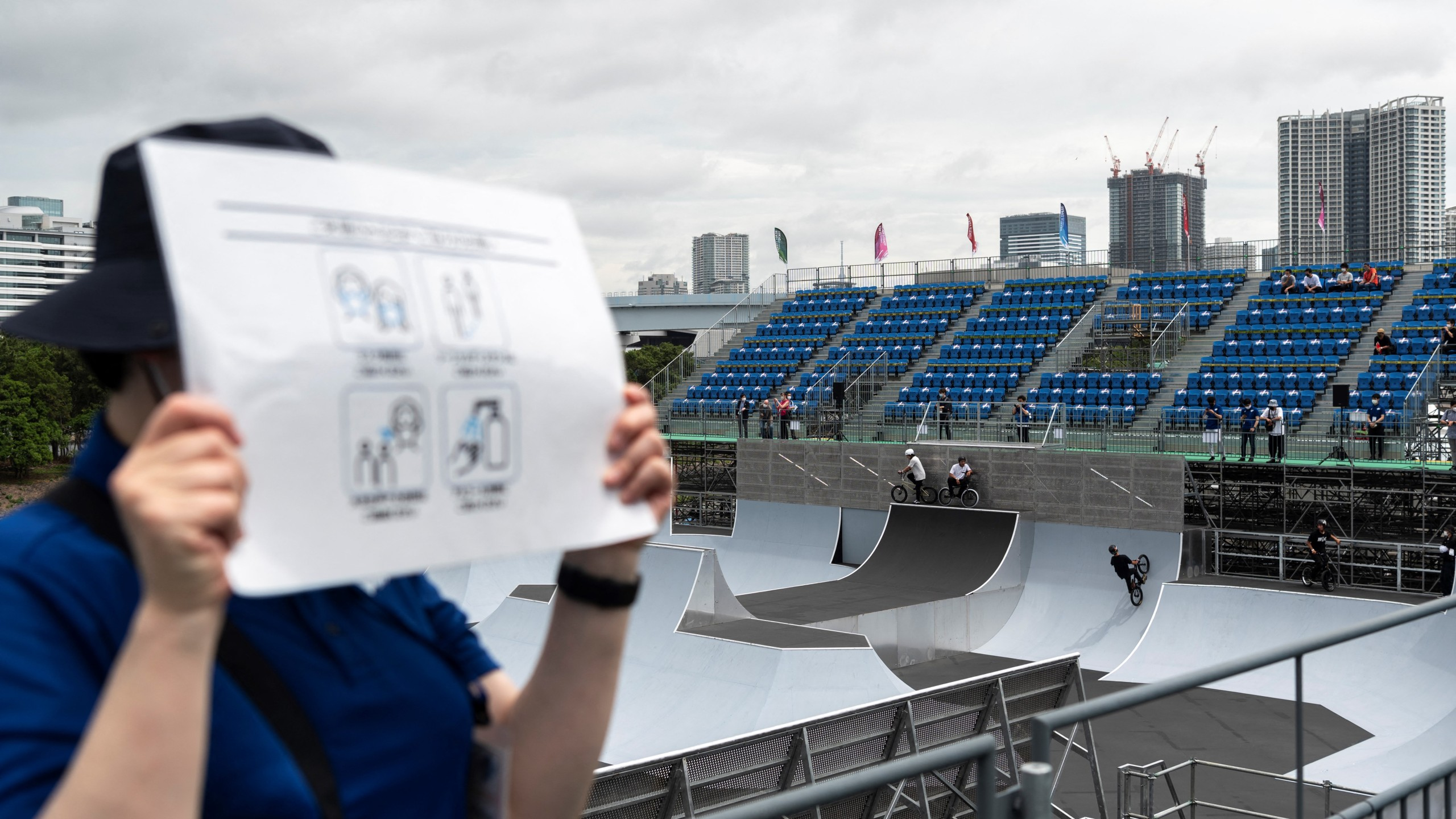A volunteer holds a poster with measures against covid19 propagation in the BMX freestyle track venue during a test event for the Tokyo 2020 Olympic Games at Ariake Urban Sports Park in Tokyo on May 17, 2021. (CHARLY TRIBALLEAU / AFP)
