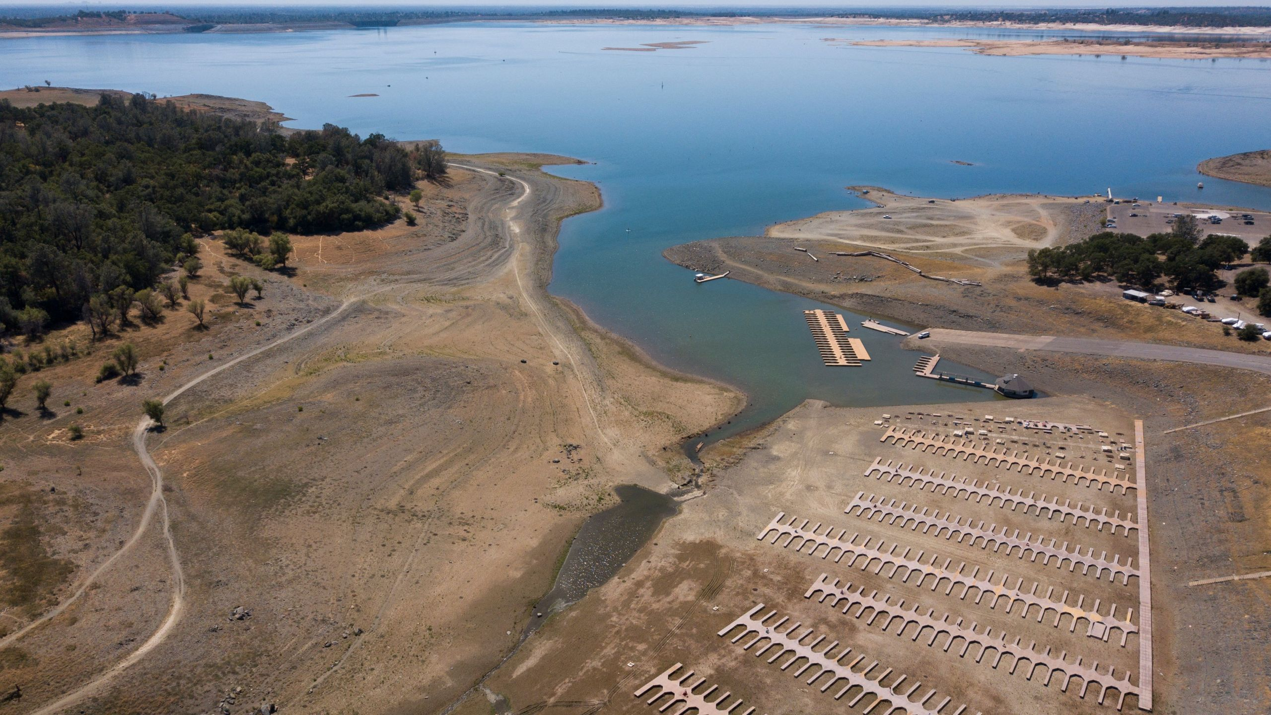 This aerial image shows empty boat slips sitting on a dry lake bed at Folsom Lake Marina as the lake experiences lower water levels during the California drought emergency on May 27, 2021 in El Dorado Hills. ( PATRICK T. FALLON/AFP via Getty Images)