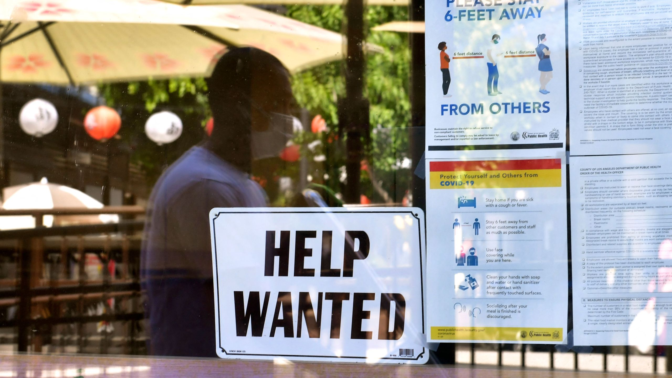 """A """"Help Wanted"""" sign is posted beside coronavirus safety guidelines in front of a restaurant in Los Angeles, California on May 28, 2021. (FREDERIC J. BROWN/AFP via Getty Images)"""