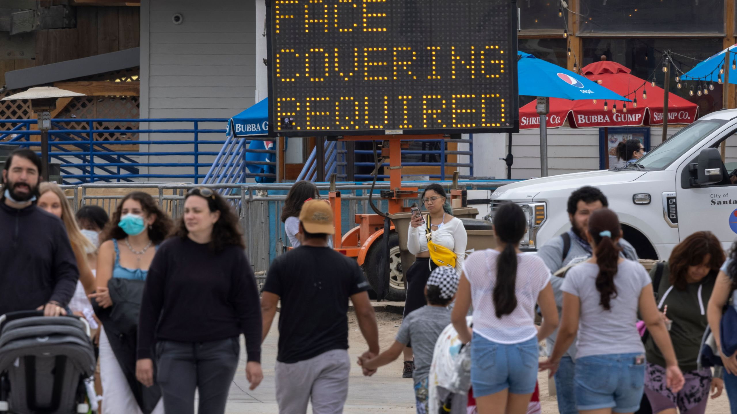People walk near the Santa Monica Pier as crowds gather on Memorial Day as shutdowns are relaxed more than a year after Covid-19 pandemic shutdowns began, in Santa Monica, California on May 31, 2021. (David McNew/AFP via Getty Images)