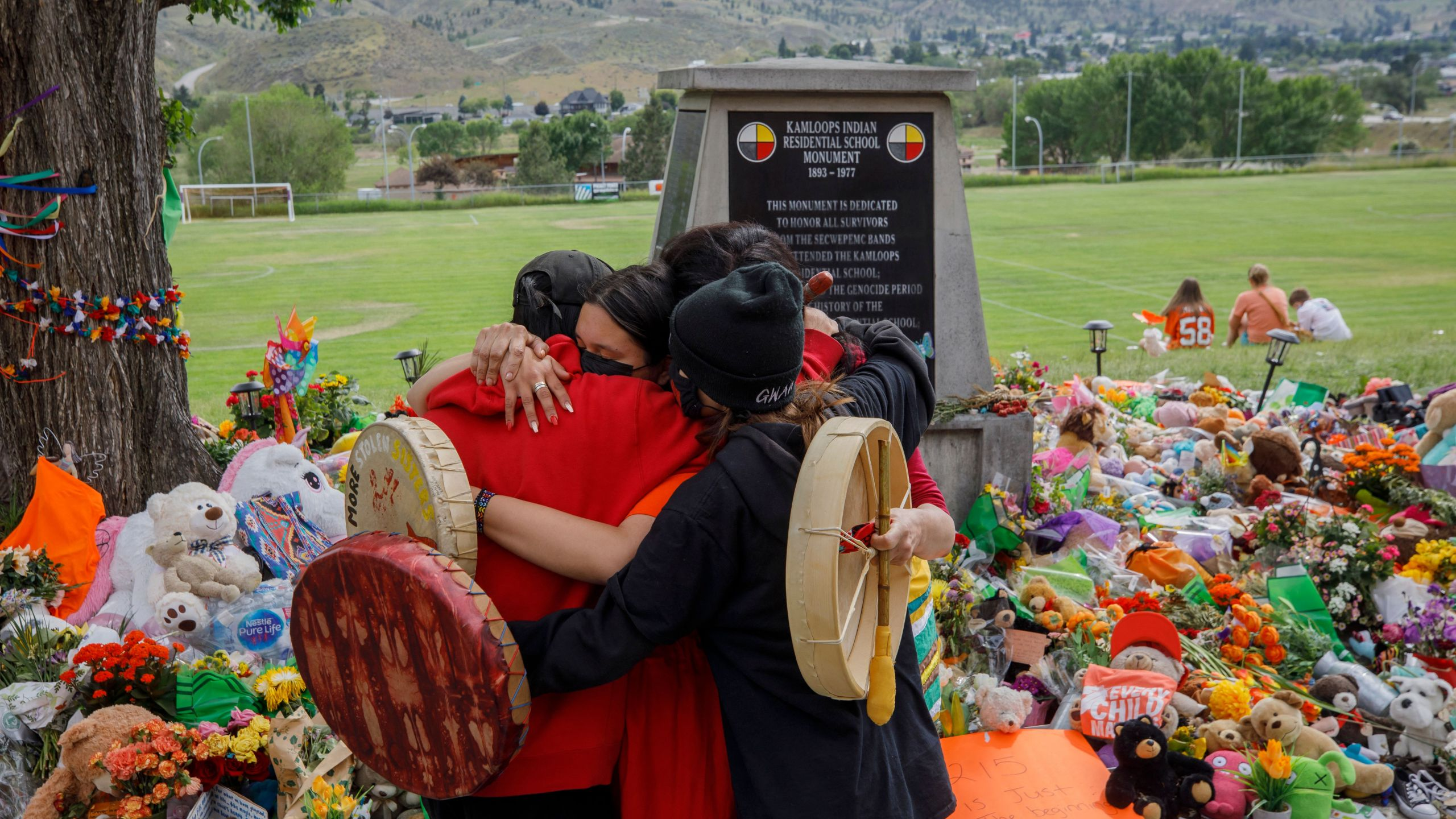People from Mosakahiken Cree Nation hug in front of a makeshift memorial at the former Kamloops Indian Residential School to honor the 215 children whose remains were recently discovered buried near the facility, in Kamloops, British Columbia, Canada, on June 4, 2021. (COLE BURSTON/AFP via Getty Images)