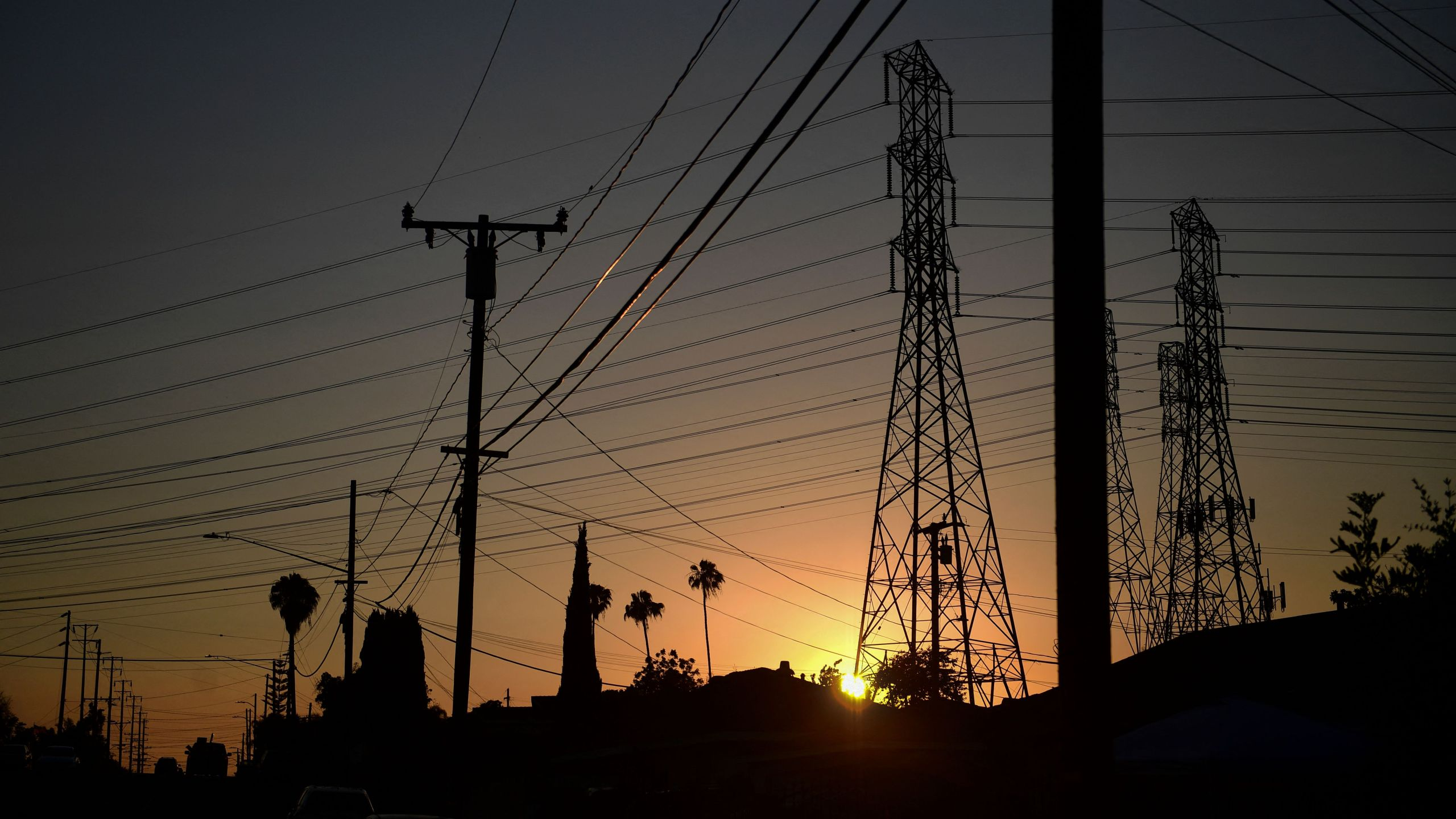 The sun sets behind power lines in Rosemead, on June 14, 2021. (FREDERIC J. BROWN/AFP via Getty Images)