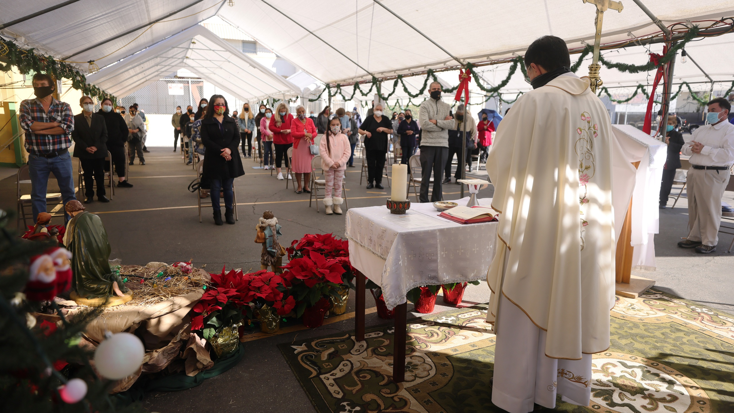 Father Rafael Saiz celebrates Christmas Mass outdoors at St. Mary's Catholic Church beneath a tent with social distancing due to the COVID-19 pandemic on December 25, 2020 in Los Angeles, California. (Mario Tama/Getty Images)