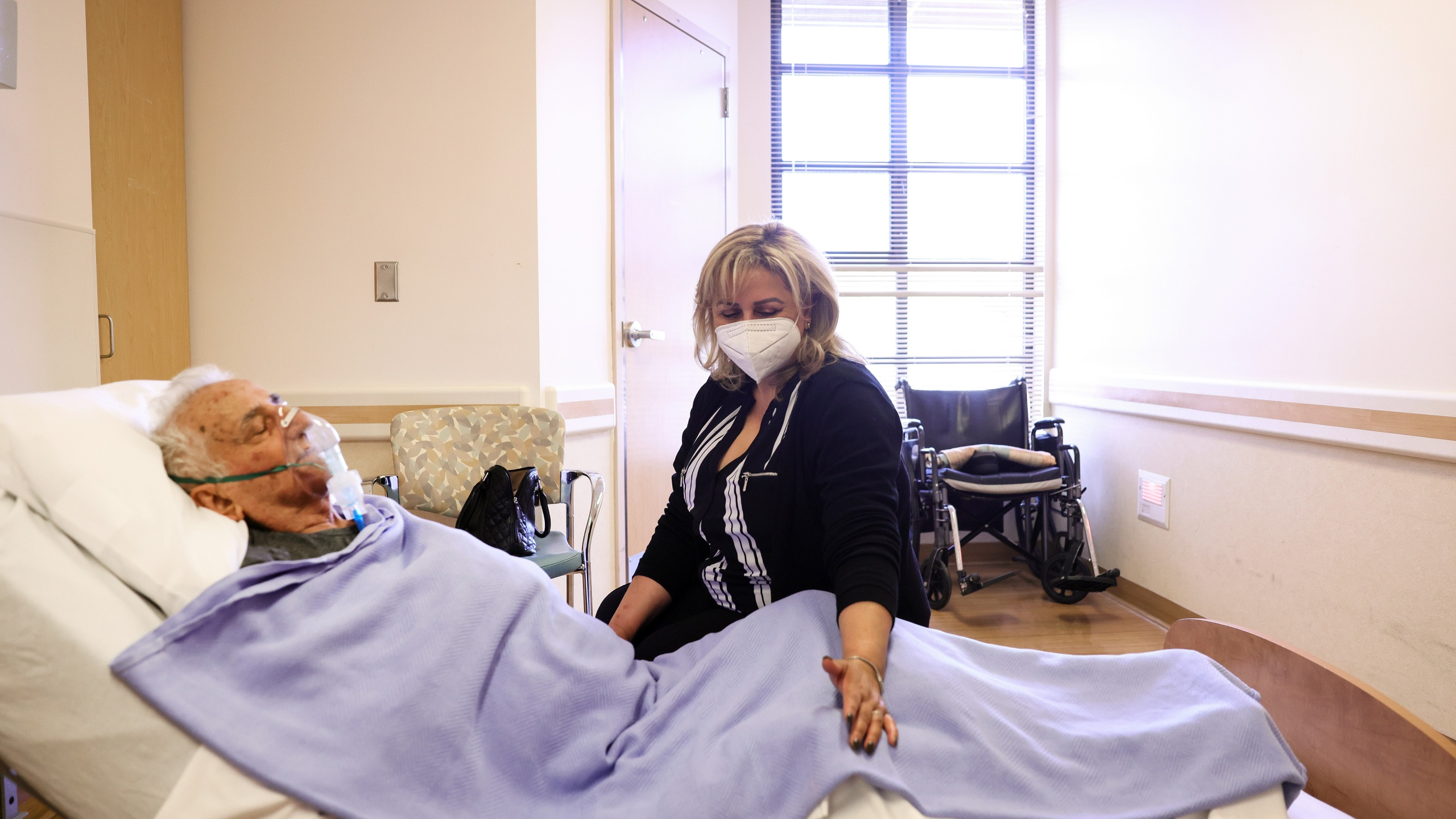 Resident Hanna Nasi is visited by daughter Surab Nasrallah on the first day of in-room family member visits at the Ararat Nursing Facility in the Mission Hills neighborhood on March 24, 2021 in Los Angeles, California. (Mario Tama/Getty Images)