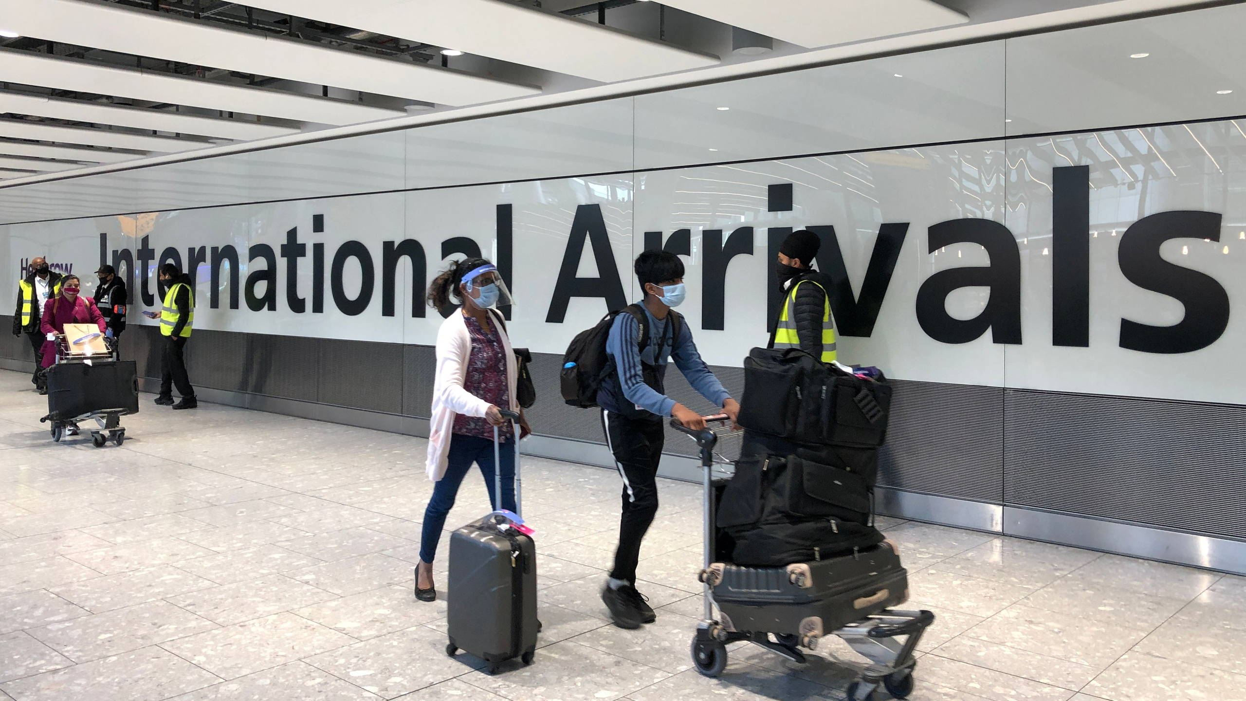 Passengers are escorted through the arrivals area of terminal 5 towards coaches destined for quarantine hotels, after landing at Heathrow airport on April 23, 2021 in London, England. (Leon Neal/Getty Images)