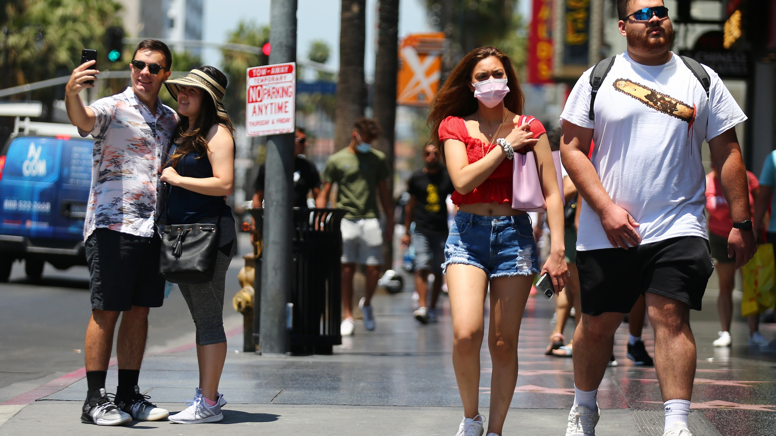 People walk and take photos on Hollywood Boulevard on June 15, 2021. (Mario Tama / Getty Images)