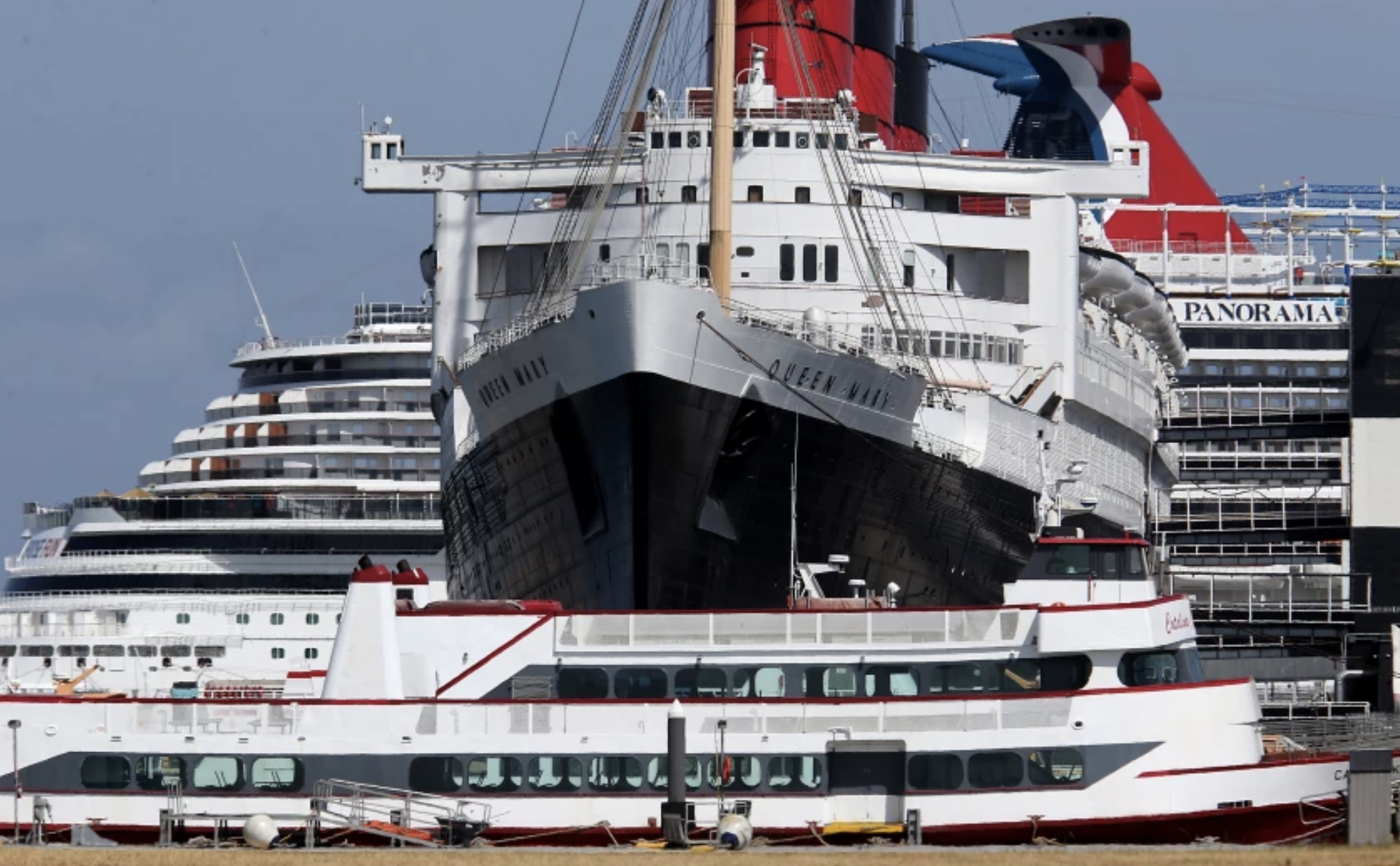 The Queen Mary is berthed between tour boats and a cruise ship in the Port of Long Beach. A new report shows the ship is in urgent need of repairs.(Luis Sinco / Los Angeles Times)