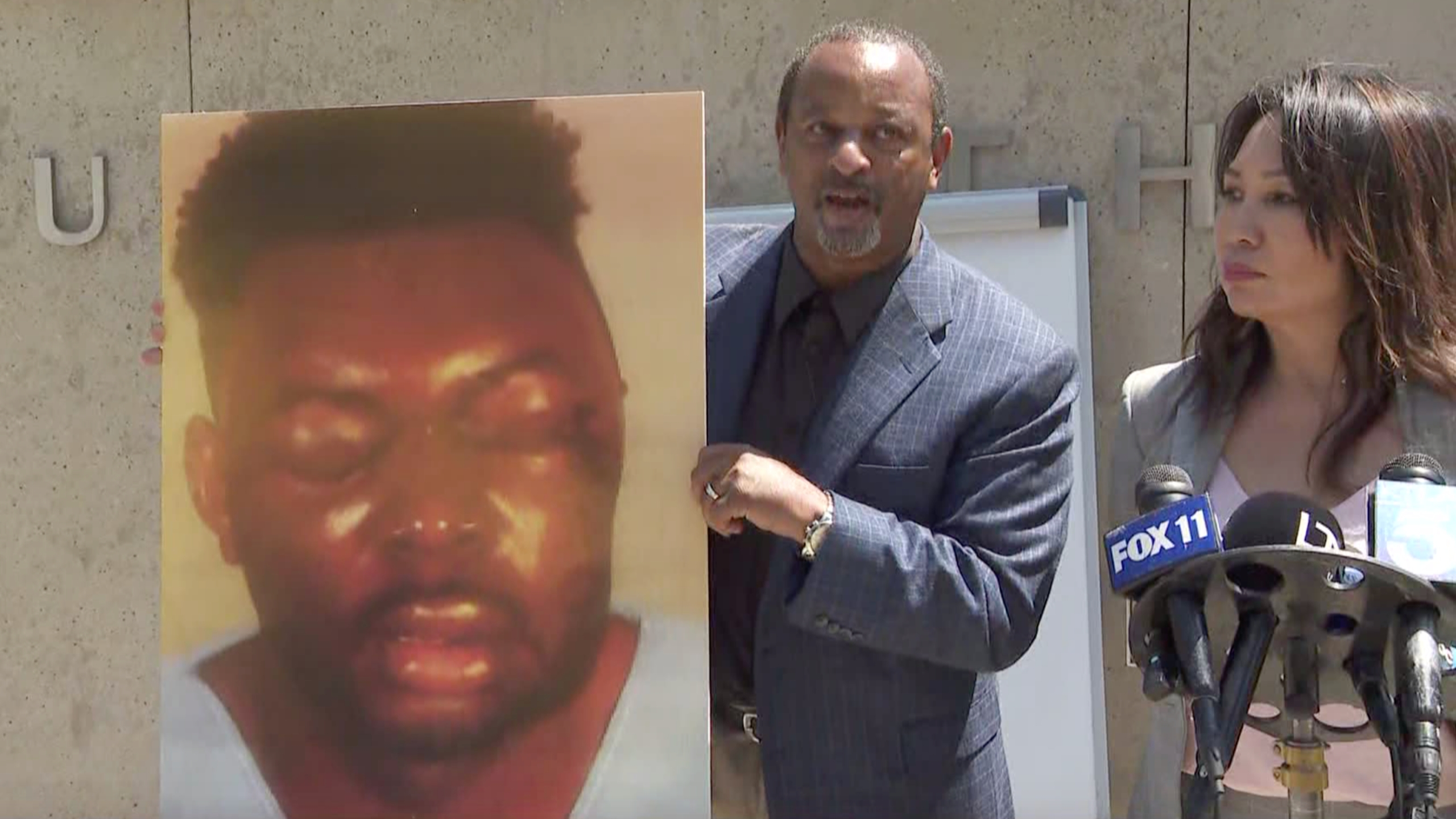 Attorneys Brian Dunn, left and Toni Jaramilla appear at a news conference in Century City on June 21, 2021, announcing a lawsuit against the Los Angeles County Sheriff's Department. Dunn holds a picture of Christopher Bailey after an alleged beating by deputies in Inglewood.