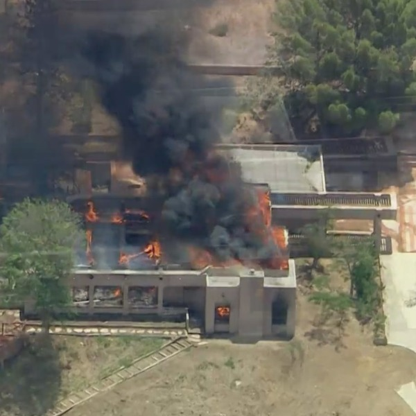 A home burns in Acton after an off-duty firefighter accused of shooting two colleagues, one fatally, was found dead there on June 1, 2021. (KTLA)