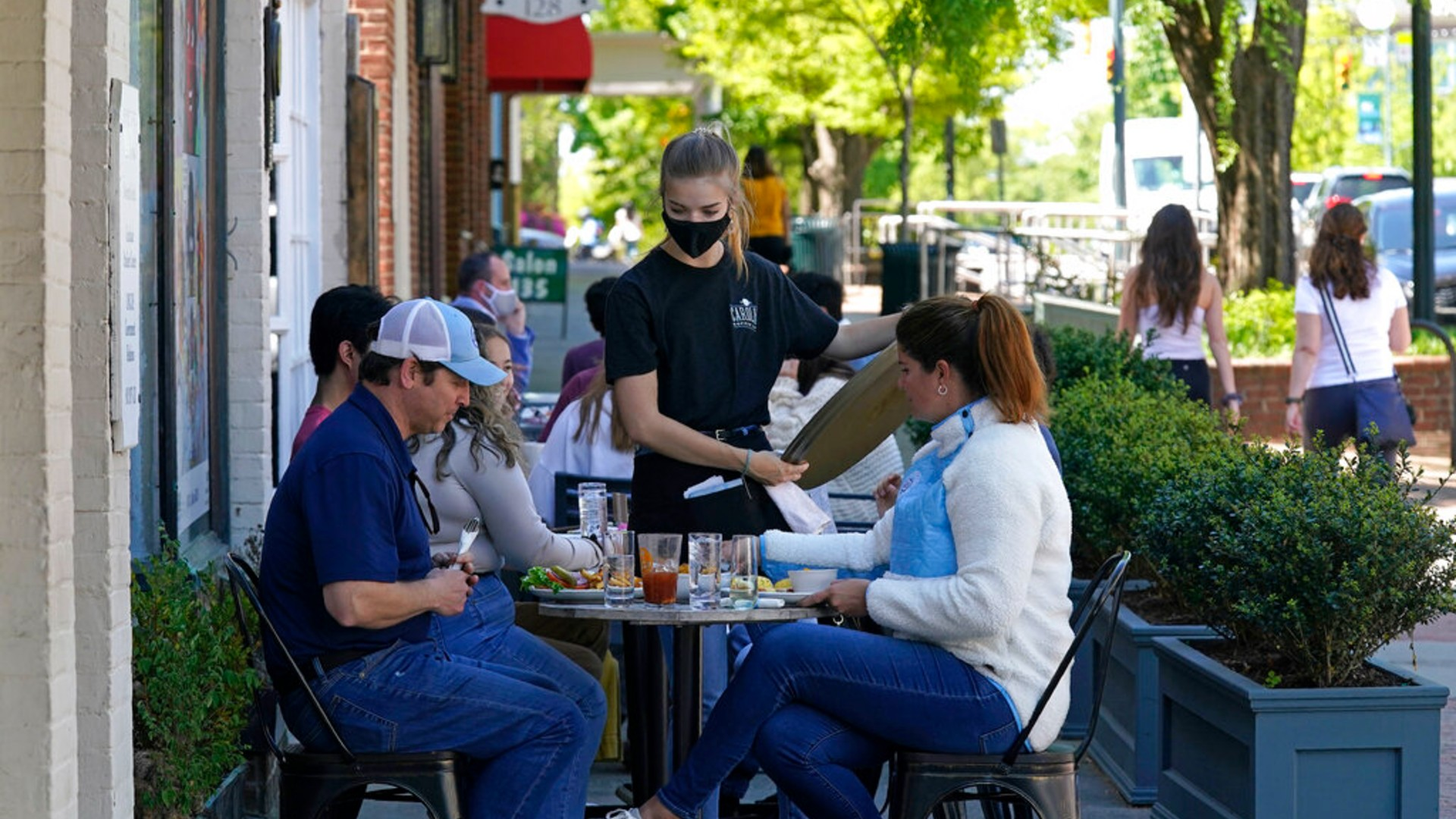 Patrons are assisted while dining along a sidewalk on Franklin Street in Chapel Hill, N.C., Friday, April 16, 2021. (AP Photo/Gerry Broome)