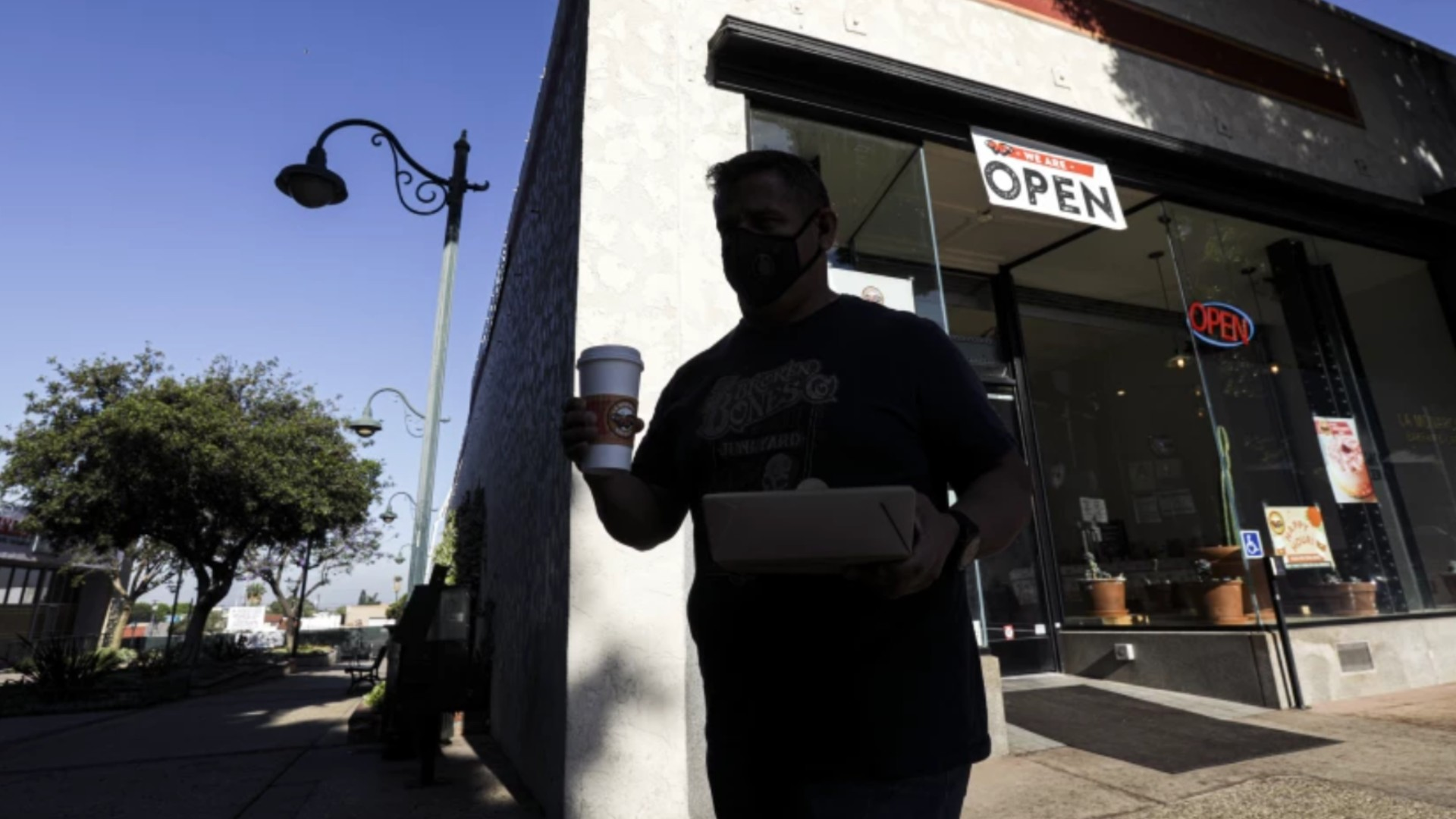 Businesses are headed for full reopening on June 15, when California drops pandemic restrictions. Economists say a consumer-spending boom will drive economic recovery. Above, David Fernandez carries his breakfast from La Monarca Bakery in Whittier last year.(Irfan Khan / Los Angeles Times)