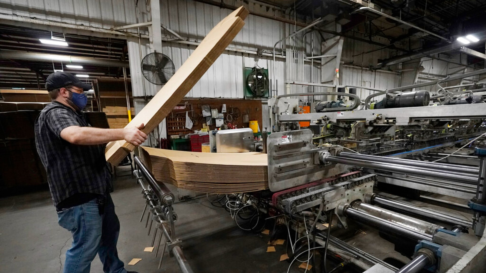 Rob Bondurant, a supervisor at Great Southern Industries, a packaging company, loads up a finishing machine in the Jackson, Miss., facility, Friday, May 28, 2021. (AP Photo/Rogelio V. Solis)
