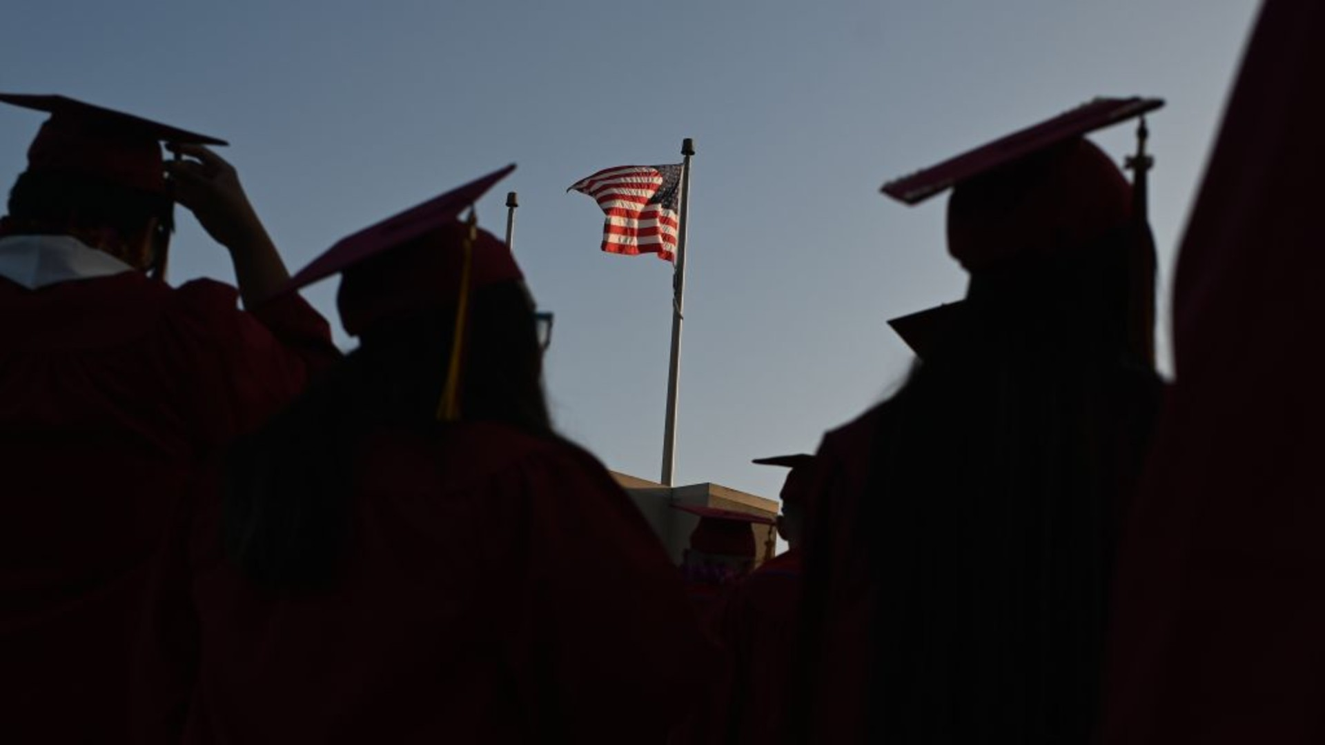 A US flag flies above a building as students earning degrees at Pasadena City College participate in the graduation ceremony, June 14, 2019, in Pasadena, California. (ROBYN BECK/AFP via Getty Images)