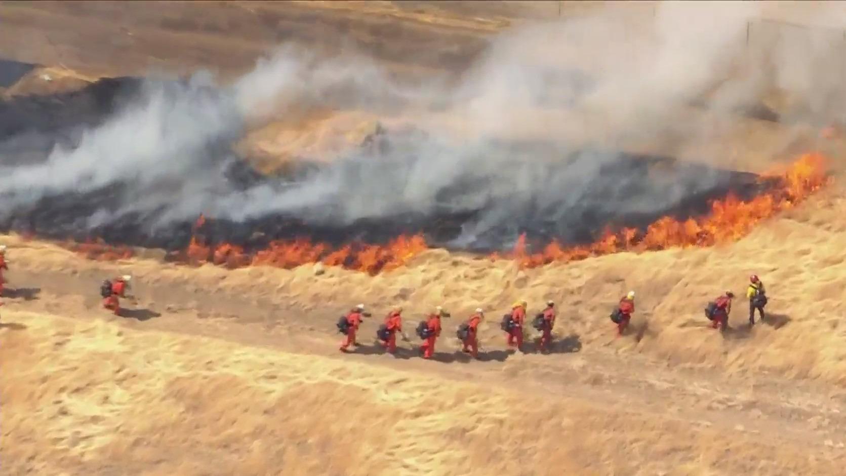 A brush fire burns in Lancaster on June 17, 2021. (KTLA)