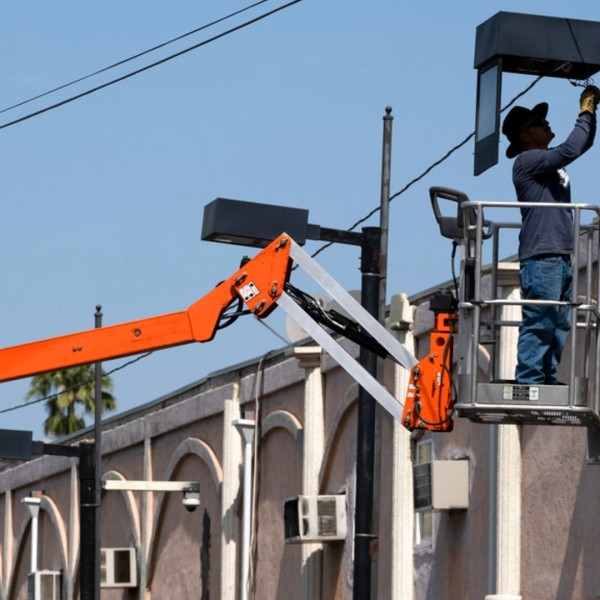 A worker fixes a street lamp in the Van Nuys section of Los Angeles on Thursday, June 17, 2021. (AP Photo/Richard Vogel)