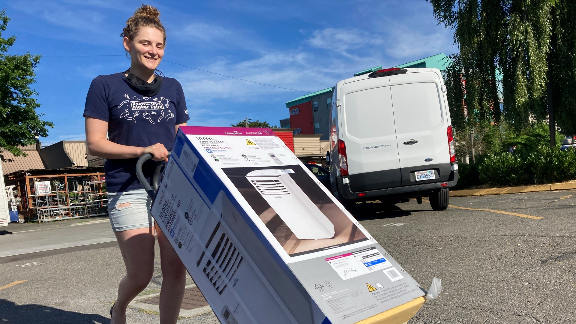 Sarah O'Sell transports her new air conditioning unit to her nearby apartment on a dolly in Seattle on Friday, June 25, 2021. (AP Photo/Manuel Valdes)