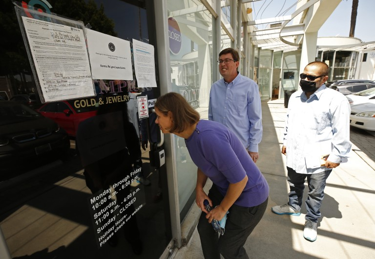 Joseph Ruiz, right, joins Jennifer Snitko and her husband Paul Snitko outside U.S. Private Vaults in Beverly Hills, where they rented safe deposit boxes. The three are among more than a dozen customers suing the federal government to recover cash and valuables seized by the FBI. (Al Seib / Los Angeles Times)