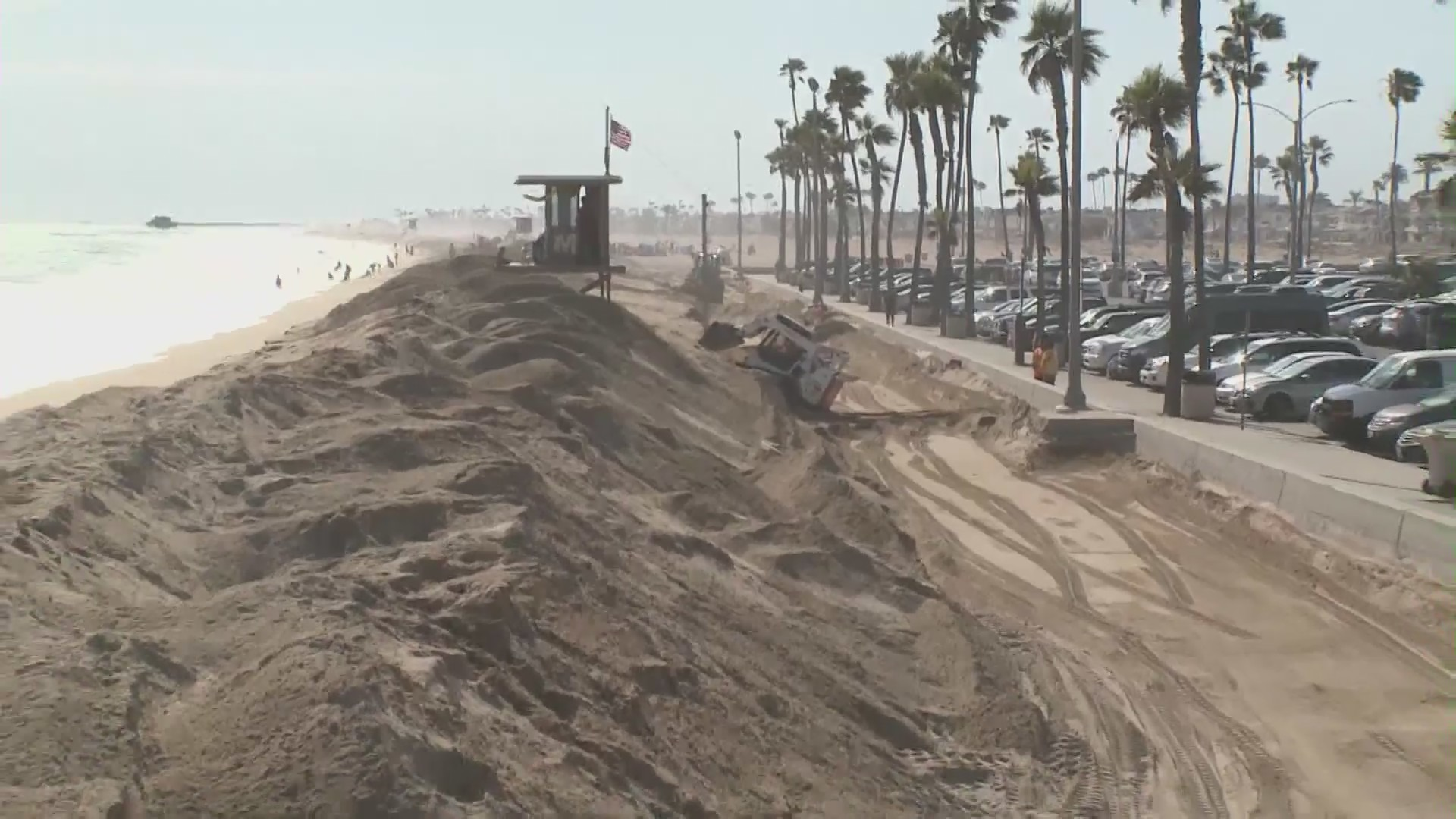 A sand berm is created in Newport Beach on June 22, 2021, in anticipation of extreme high tides that pose a flood threat. (KTLA)