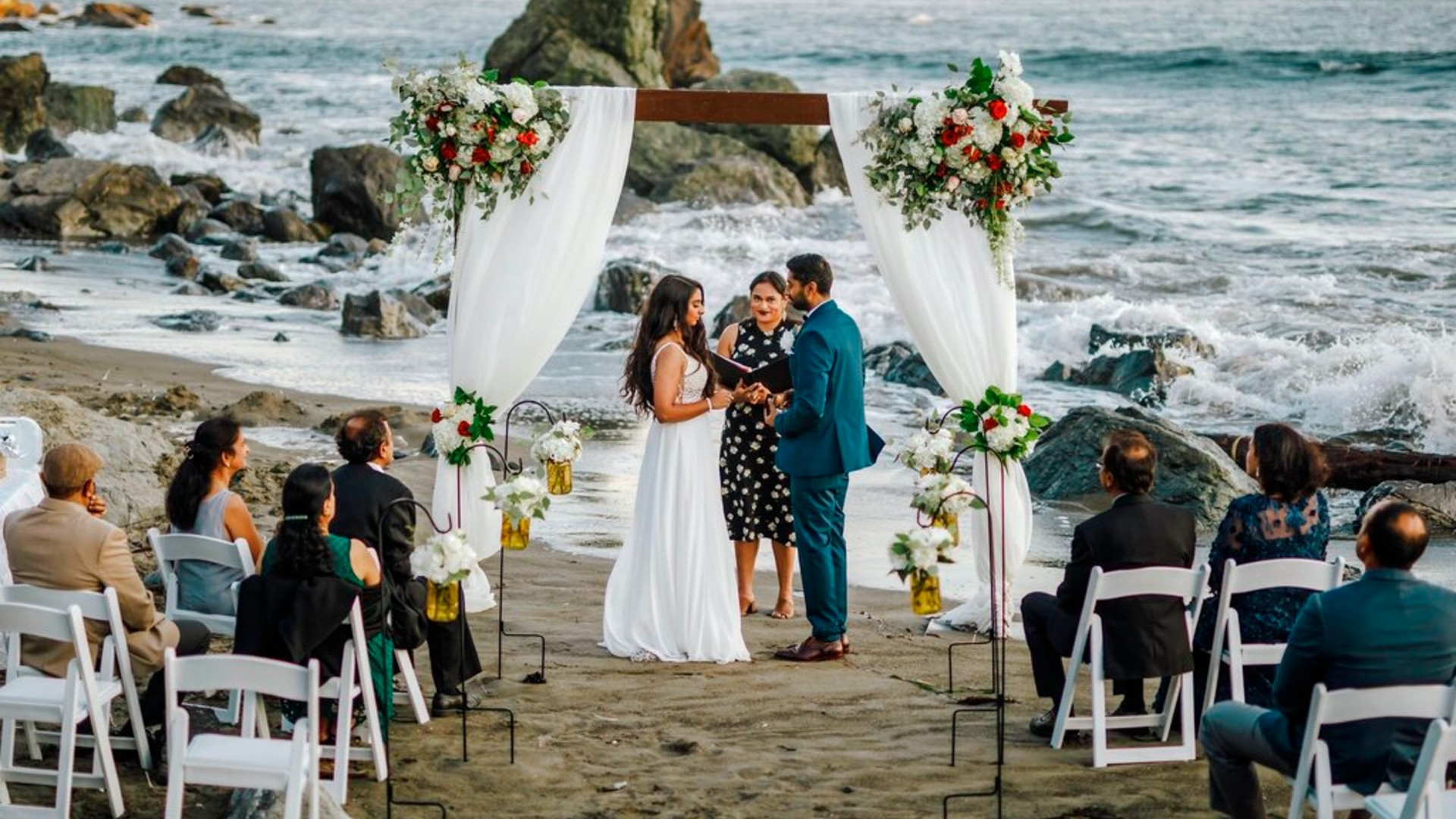 This photo shows bride Namisha Balagopal and groom Suhaas Prasad getting married in a small legal ceremony Aug. 15, 2020, on Muir Beach near San Francisco. (Vellora Productions via AP)