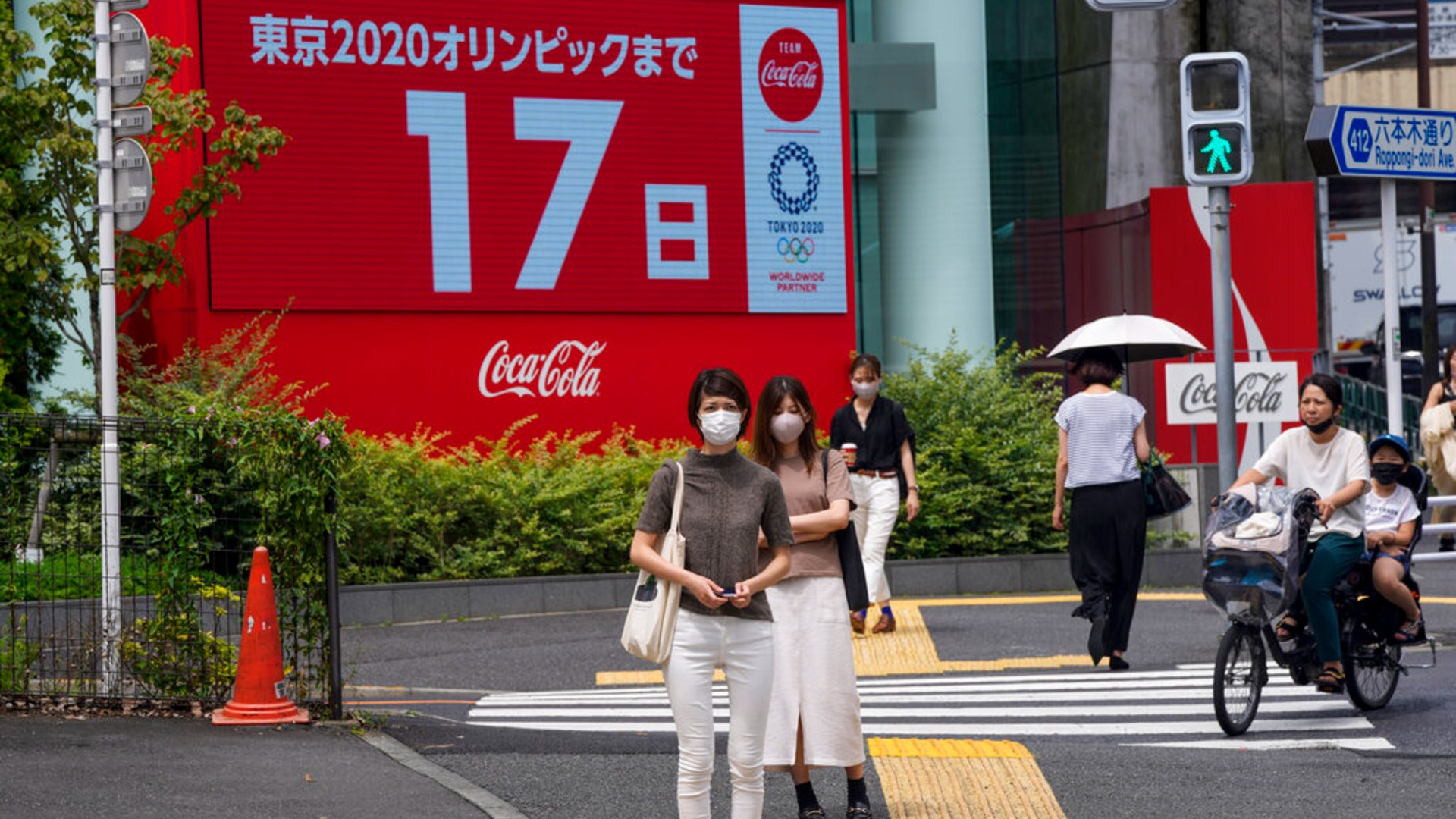 People wearing protective masks wait at a crosswalk as an electric display in the background shows 17 days to Tokyo 2020 Olympics Tuesday, July 6, 2021, in Tokyo. (AP Photo/Kiichiro Sato)