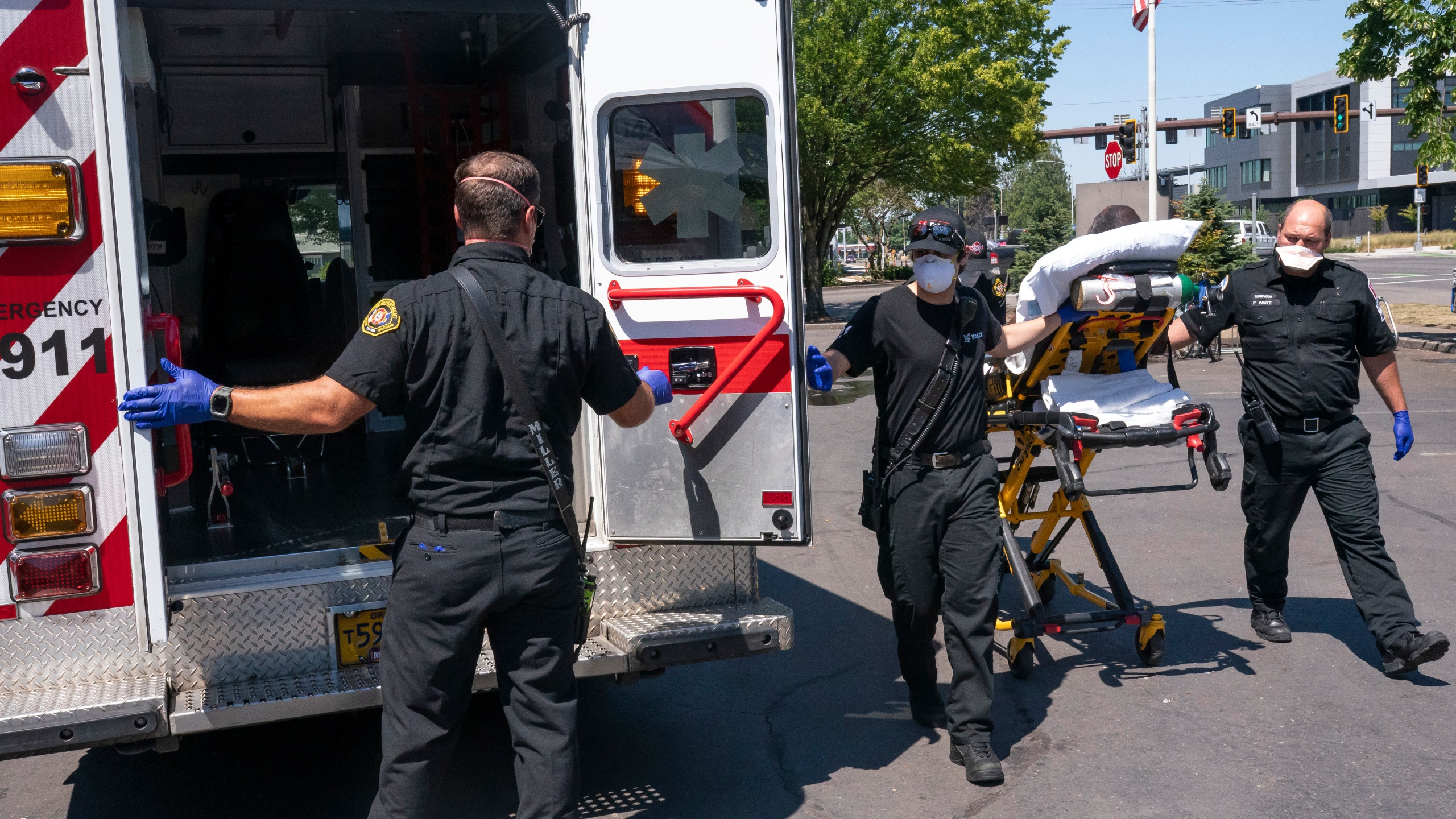 Salem Fire Department paramedics and employees of Falck Northwest ambulances respond to a heat exposure call during a heat wave, Saturday, June 26, 2021, in Salem, Ore. (AP Photo/Nathan Howard)