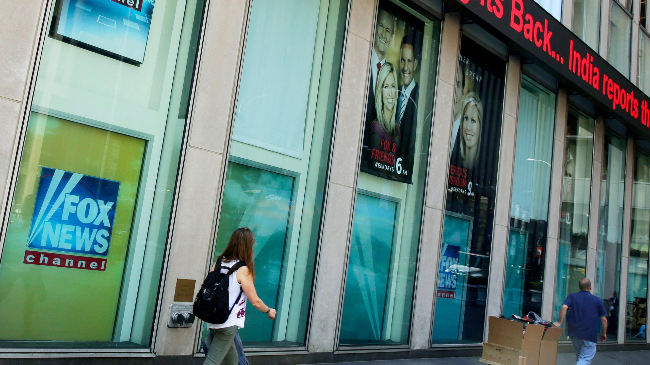 People pass the News Corporation headquarters building and Fox News studios in New York on Aug. 1, 2017. (AP Photo/Richard Drew, File)
