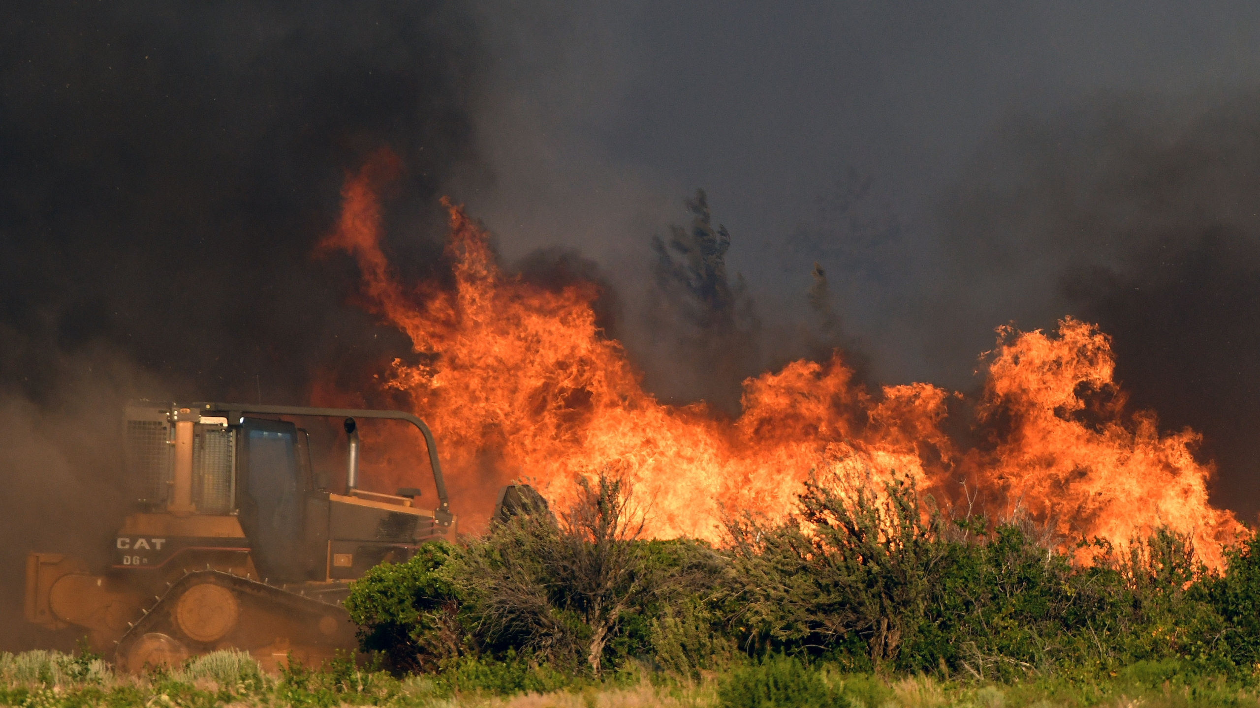 A bulldozer operator works on a fire line as vegetation burns nearby at the Lava Fire on Monday, June 28, 2021, north of Weed, Calif. Officers shot and killed a man who pulled a gun as they tried to keep him out of a complex of marijuana farms in an area of far Northern California where thousands of people have been ordered to evacuate because of a raging wildfire. (Scott Stoddard/Grants Pass Daily Courier via AP)