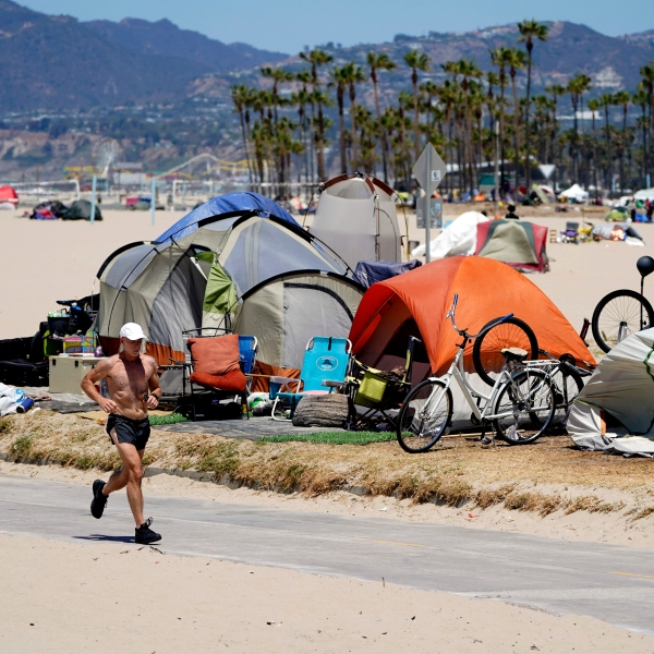 In this June 8, 2021, file photo, a jogger walks past a homeless encampment in the Venice Beach section of Los Angeles. (AP Photo/Marcio Jose Sanchez, File)