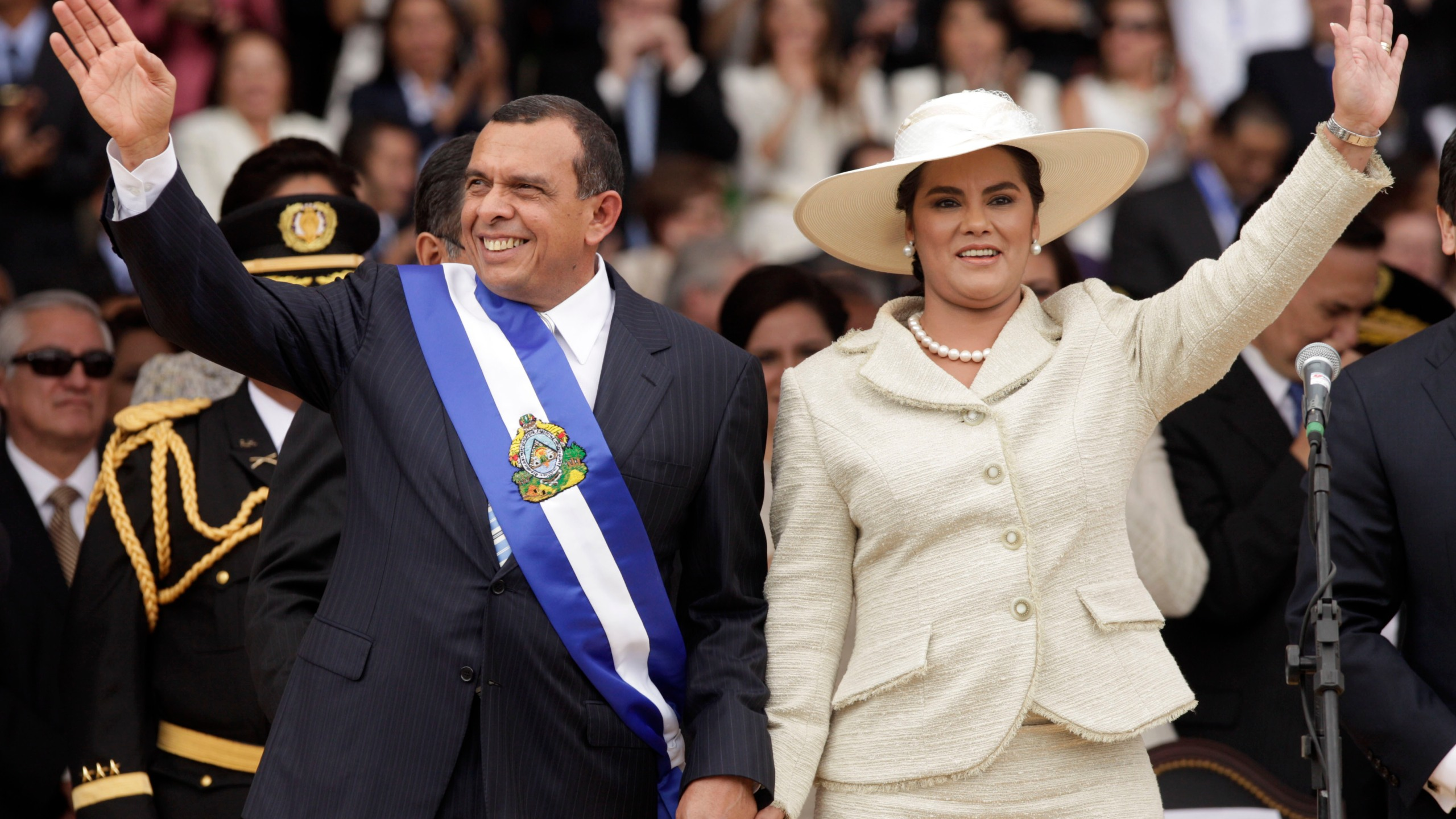 In this Jan. 27, 2010 file photo, wearing the presidential sash, Honduran President Porfirio Lobo and his wife First Lady Rosa Elena wave after Lobo was sworn in as the new president during his inauguration ceremony in Tegucigalpa. (AP Photo/Arnulfo Franco, File)