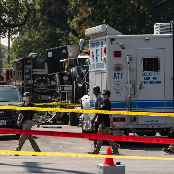 Investigators walk past an armored Los Angeles Police Department tractor-trailer July 1, 2021 in Los Angeles. (AP Photo/Damian Dovarganes)