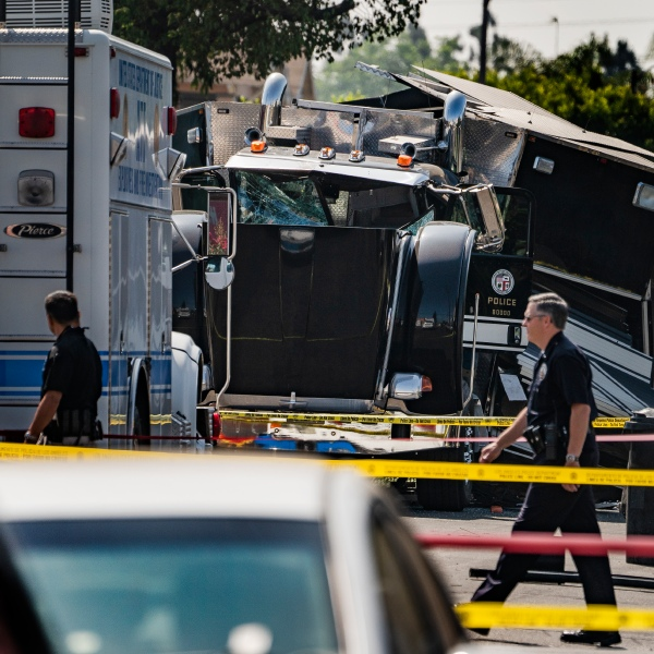 Police officers walk past the remains of an armored Los Angeles Police Department tractor-trailer on July 1, 2021, the morning after illegal fireworks seized at a South Los Angeles home exploded. (Damian Dovarganes / Associated Press)