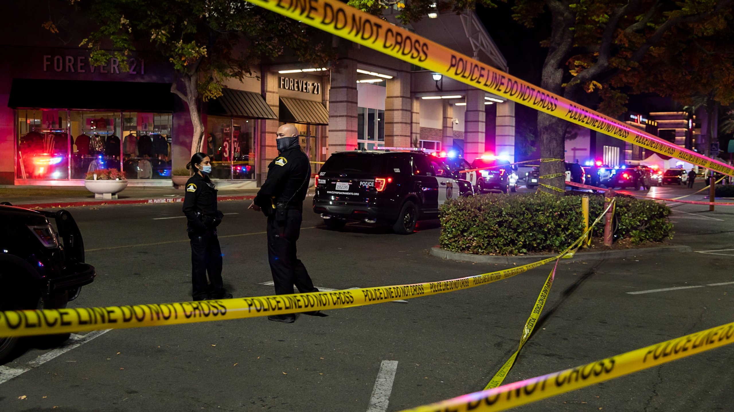 In this Nov. 27, 2020 file photo Police stand outside Arden Fair Mall after a shooting that left one person dead and another critically injured in Sacramento, Calif. Homicides in California jumped 31% last year, the deadliest year since 2007, according to a report issued by the state attorney general's office, Thursday, July 1, 2021. (Paul Kitagaki Jr./The Sacramento Bee via AP, File)