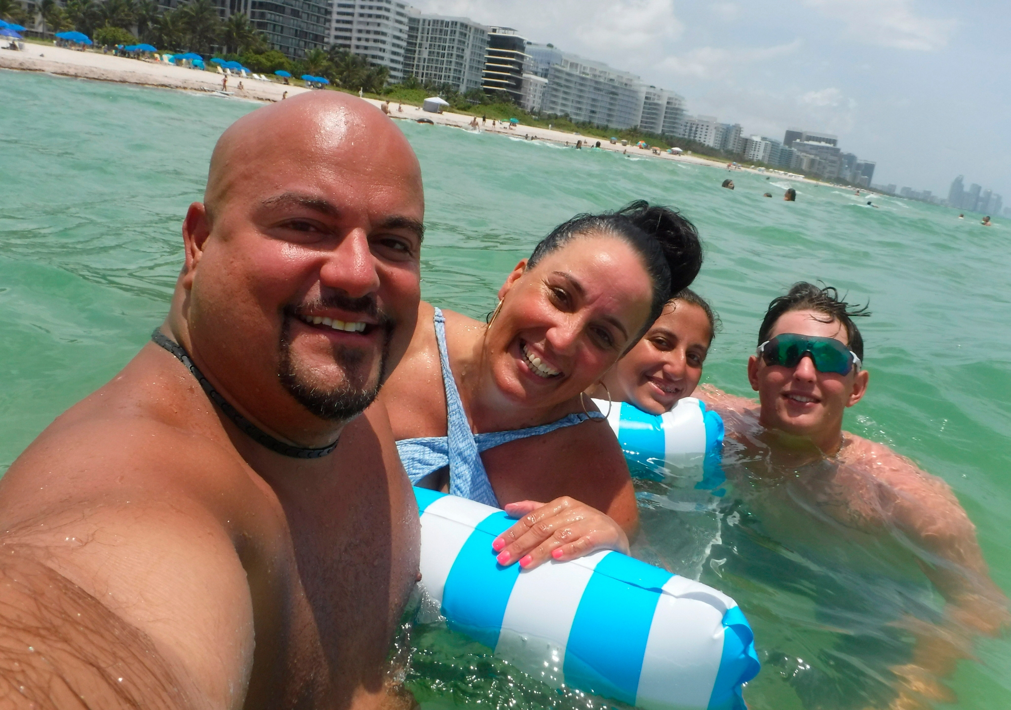 """This Wednesday, June 23, 2021, photo provided by Albert Aguero shows him, his wife, Janette; 14-year-old daughter, Athena, and 22-year-old son, Justin Willis, vacationing in the Miami area from New Jersey. They all were able to escape the building collapse of Champlain Towers South the following day. """"When I opened the staircase door and half the staircase was missing, at that point I know we're racing against time to all get out as a family,"""" Albert Aguero says. (Albert Aguero via AP)"""