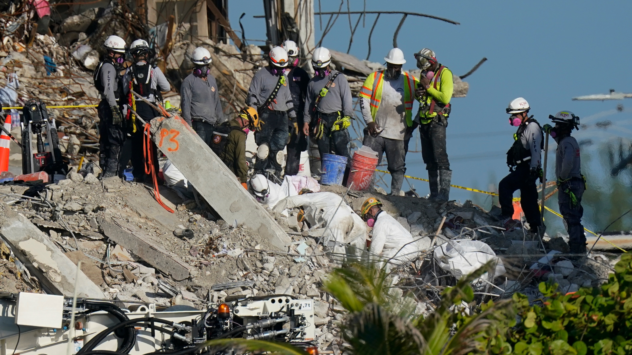 A team works to extricate remains as search and rescue personnel look on, atop the rubble at the Champlain Towers South condo building where scores of people remain missing more than a week after it partially collapsed, Friday, July 2, 2021, in Surfside, Fla. Rescue efforts resumed Thursday evening after being halted for most of the day over concerns about the stability of the remaining structure.(AP Photo/Mark Humphrey)