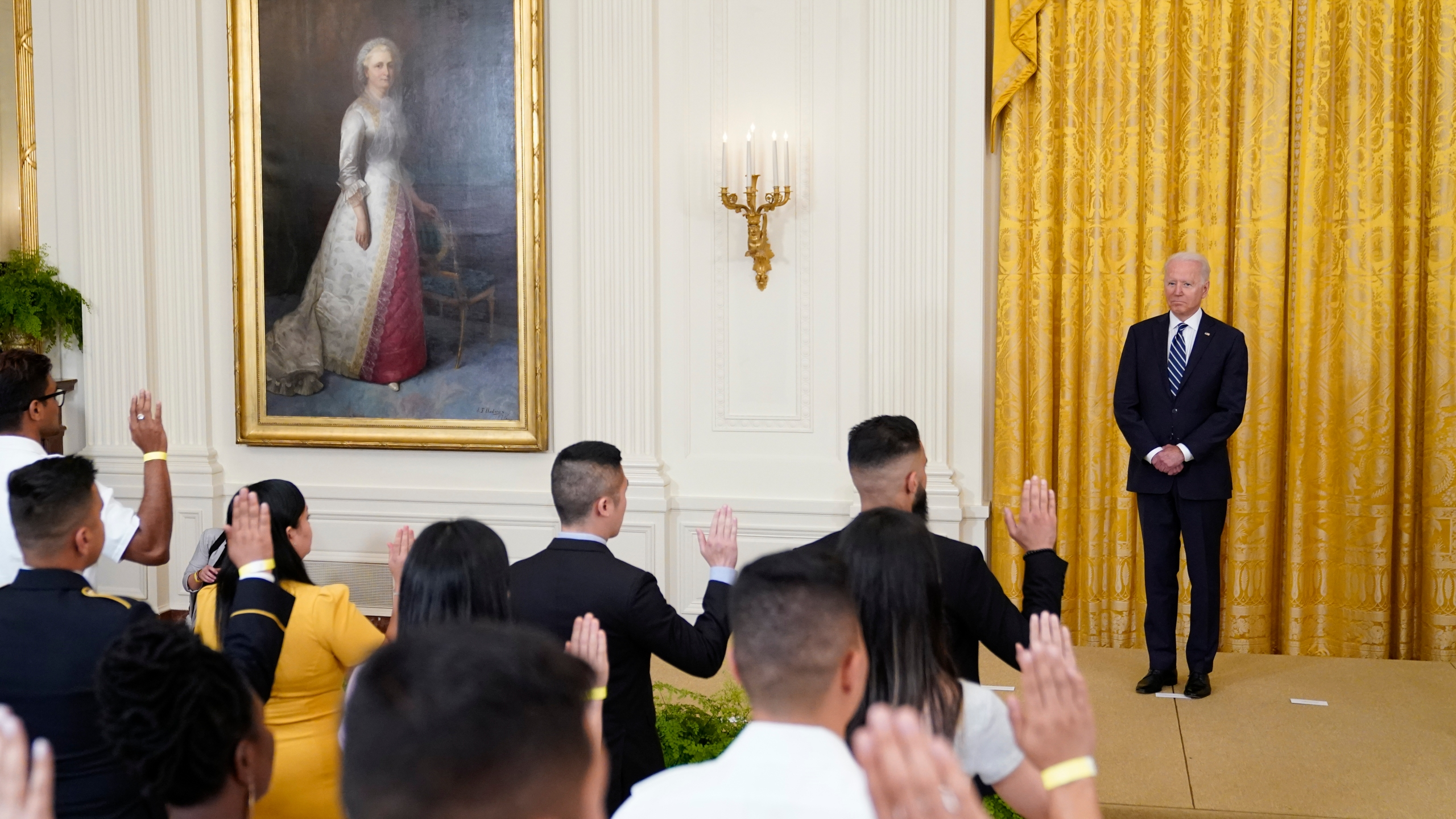 President Joe Biden listens as people take the Oath of Allegiance during a naturalization ceremony in the East Room of the White House, Friday, July 2, 2021, in Washington. (AP Photo/Patrick Semansky)